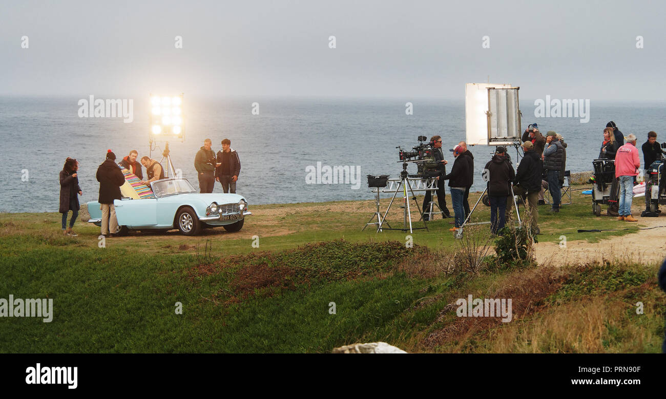 Newquay, UK. 3rd Oct 2018. Rosamunde Pilcher`s story The Secret Suitcase filming at Fistral Beach Cornwall.Actors Michaela Saba and Max Engelke are seen in a classic Triumph TR4 sport car perched on the cliff.The German company FFP New Media production is for ZDF channel   03rd,October, 2018,  Robert Taylor/Alamy live news Newquay, Cornwall, UK. Credit: Robert Taylor/Alamy Live News - Stock Image