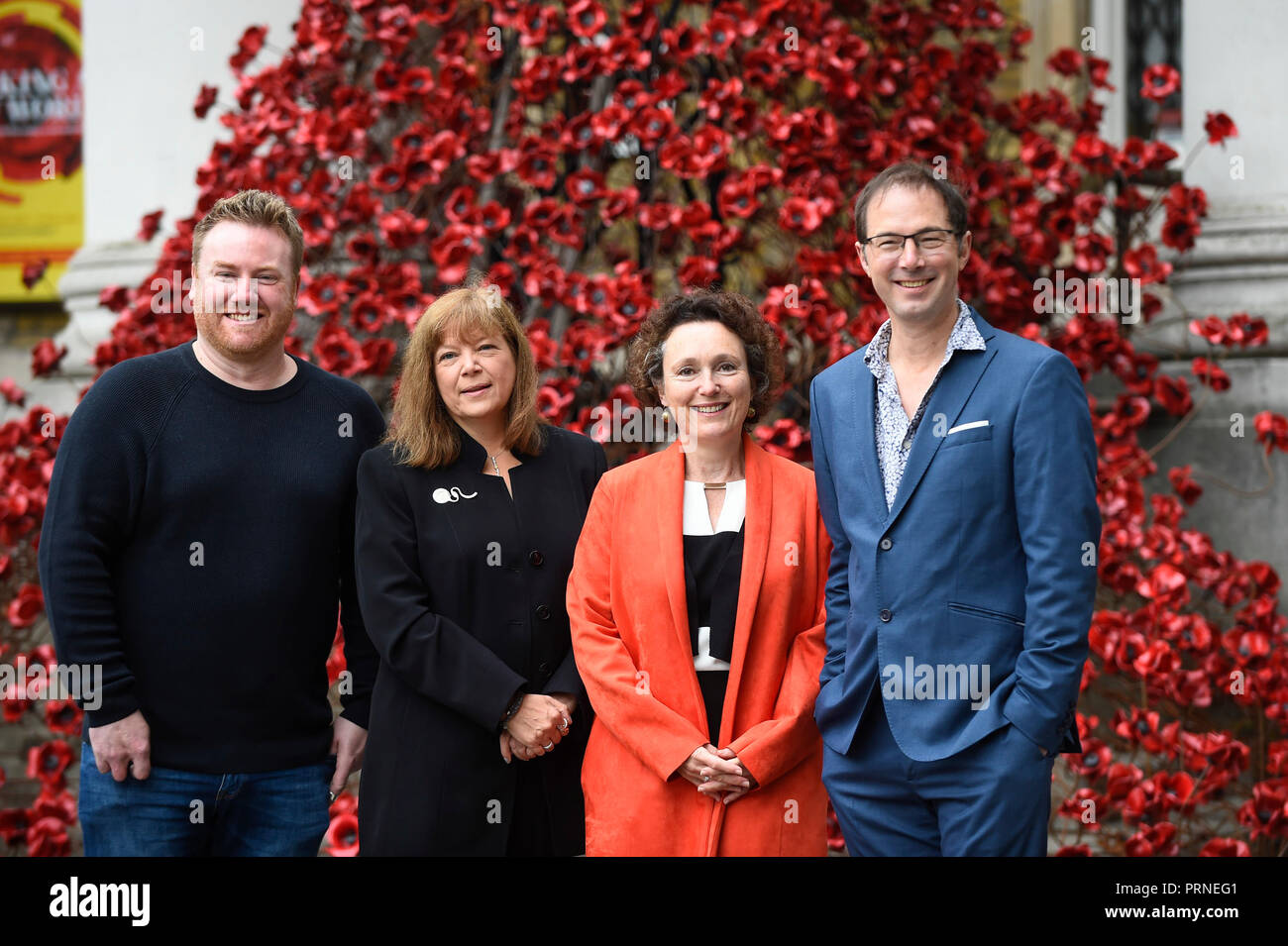 London, UK.  4 October 2018. (L to R) Artist Paul Cummins,  Diane Lees, Director General IWM, Jenny Waldman, artistic director of 14-18 NOW and designer Tom Piper stand next to  'Weeping Window', the iconic poppy sculpture which is unveiled at the Imperial War Museum.  The sculpture will be on site until 18 November 2018.  Credit: Stephen Chung / Alamy Live News - Stock Image