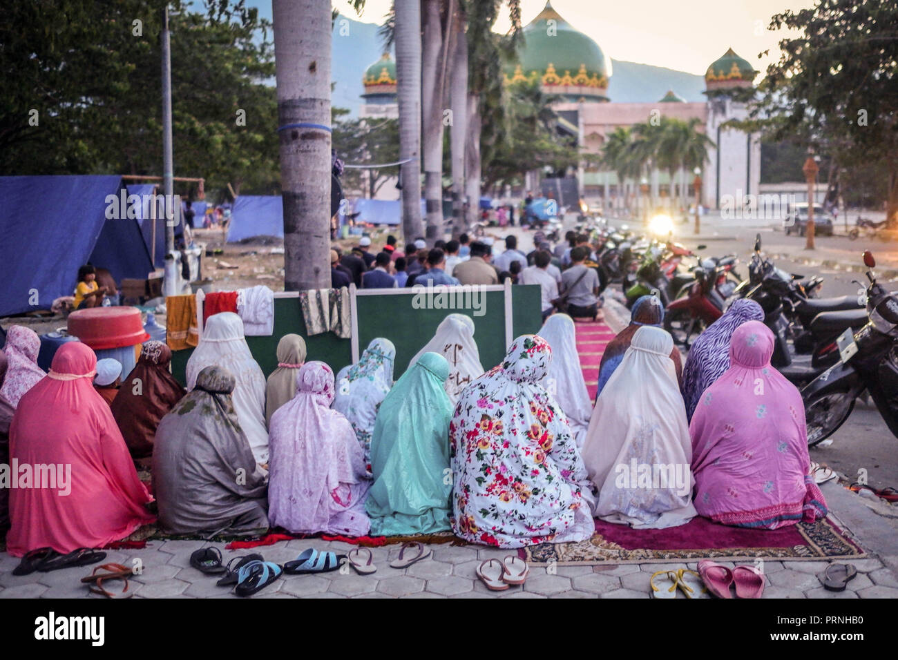 Palu, Indonesia. 4th Oct 2018. Female refugees seen praying in in the Lere Refugee settlement. A deadly earthquake measuring 7.7 magnitude and the tsunami wave caused by it has destroyed the city of Palu and much of the area in Central Sulawesi. According to the officials, death toll from devastating quake and tsunami rises to 1,347, around 800 people in hospitals are seriously injured and some 62,000 people have been displaced in 24 camps around the region. Credit: SOPA Images Limited/Alamy Live News - Stock Image