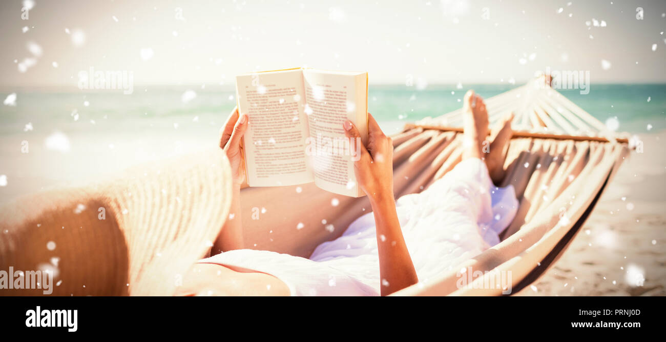 Composite image of woman reading book on hammock at beach - Stock Image