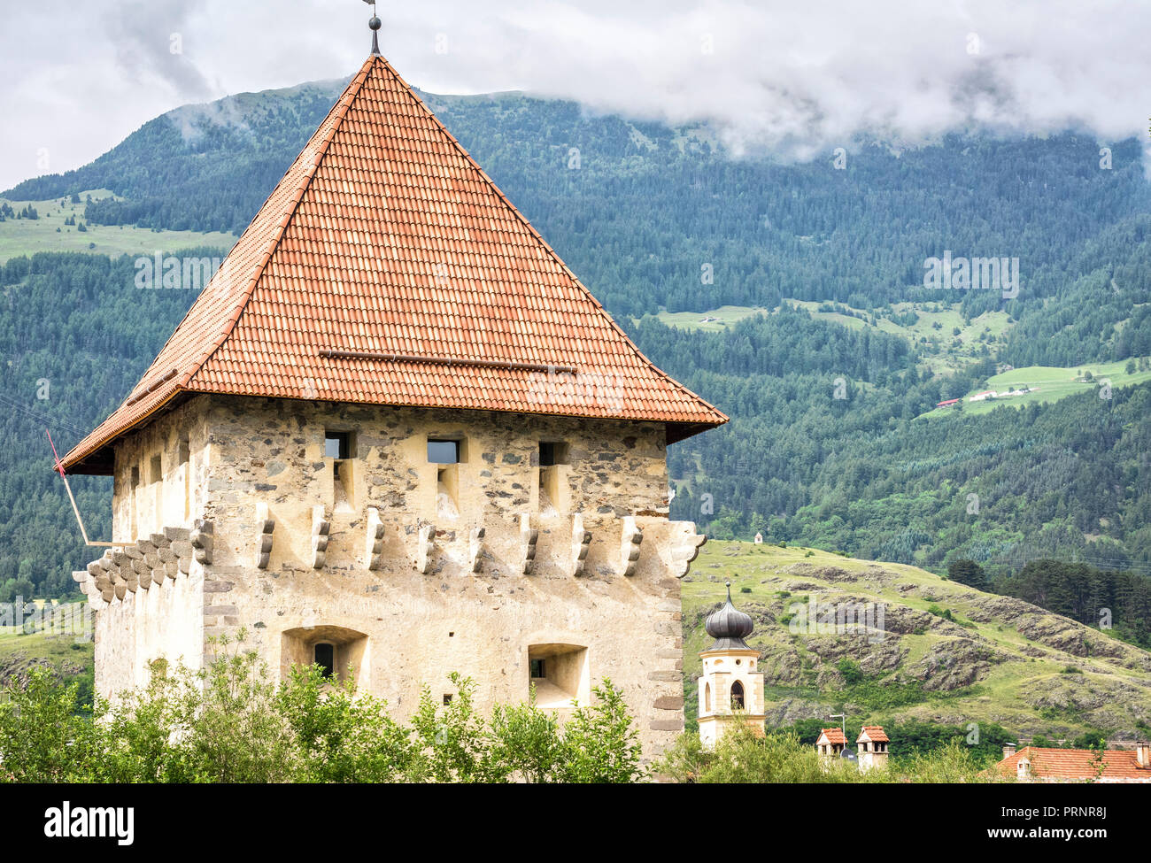 Glorenza (Glums) in South Tyrol/Trentino Alto Adige, Italy. Church tower with the city walls - Stock Image
