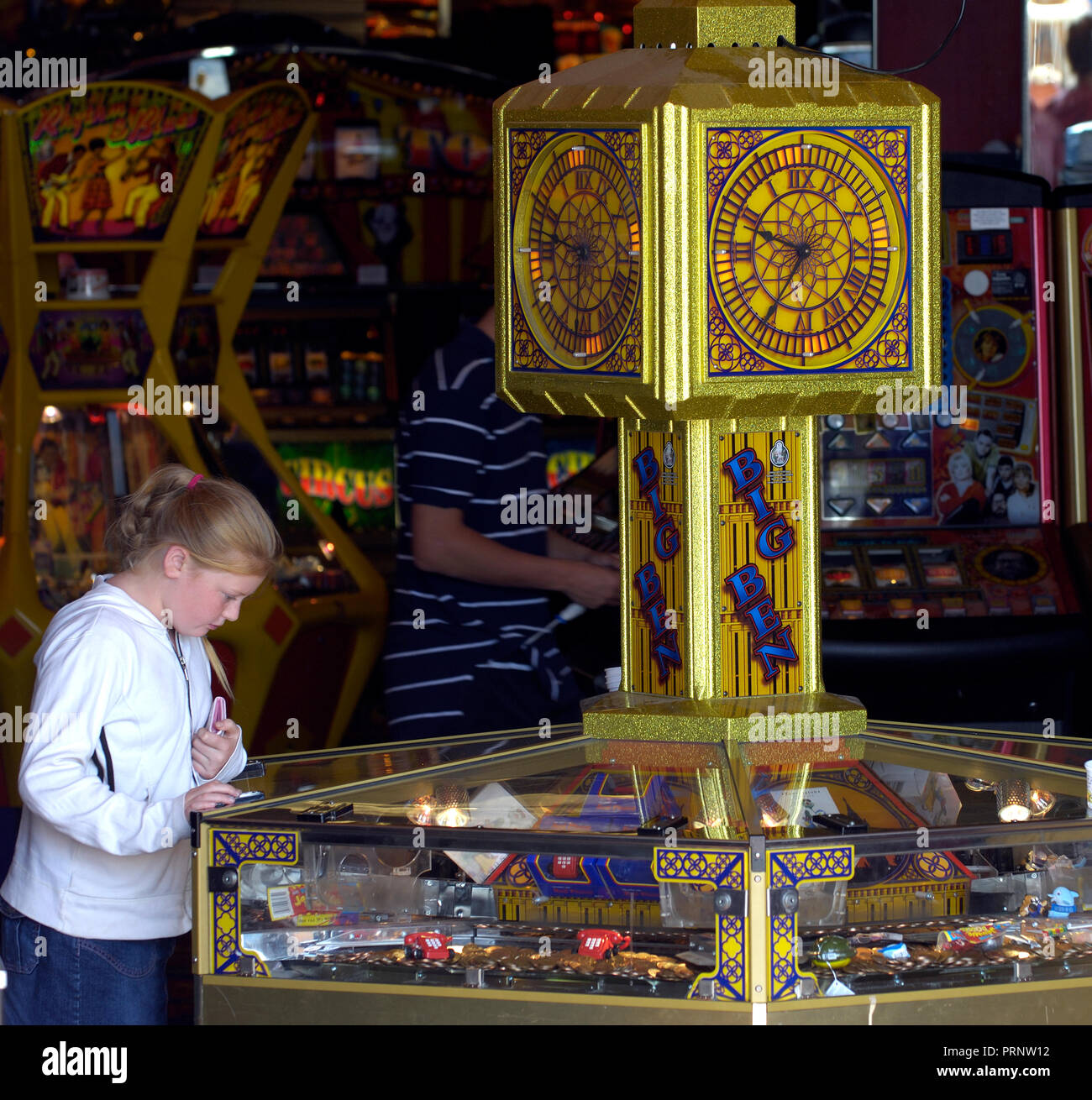 Young girl plating an amusement machine in a seaside arcade, England, UK - Stock Image
