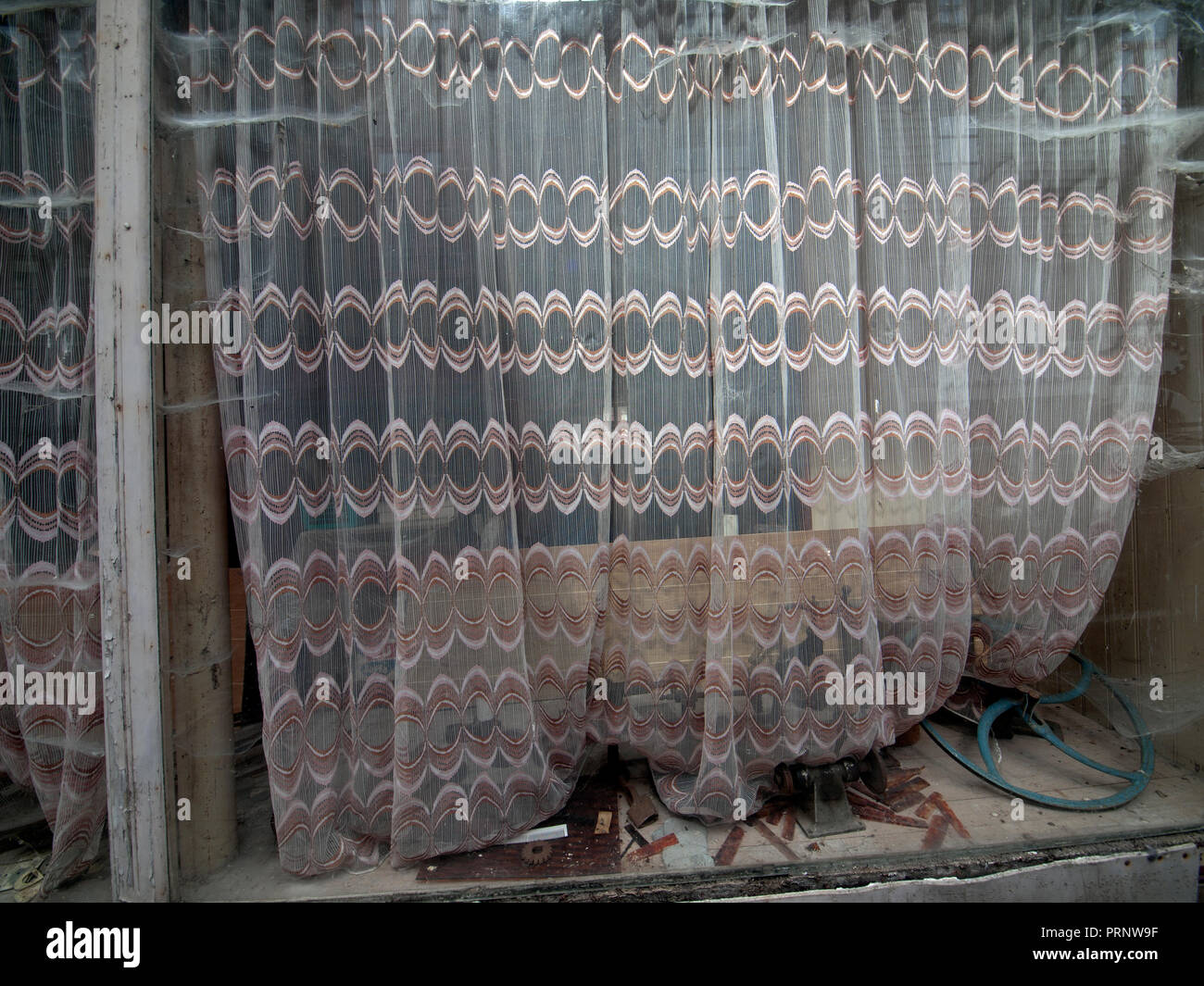 Net curtains in a run down French shop window - Stock Image