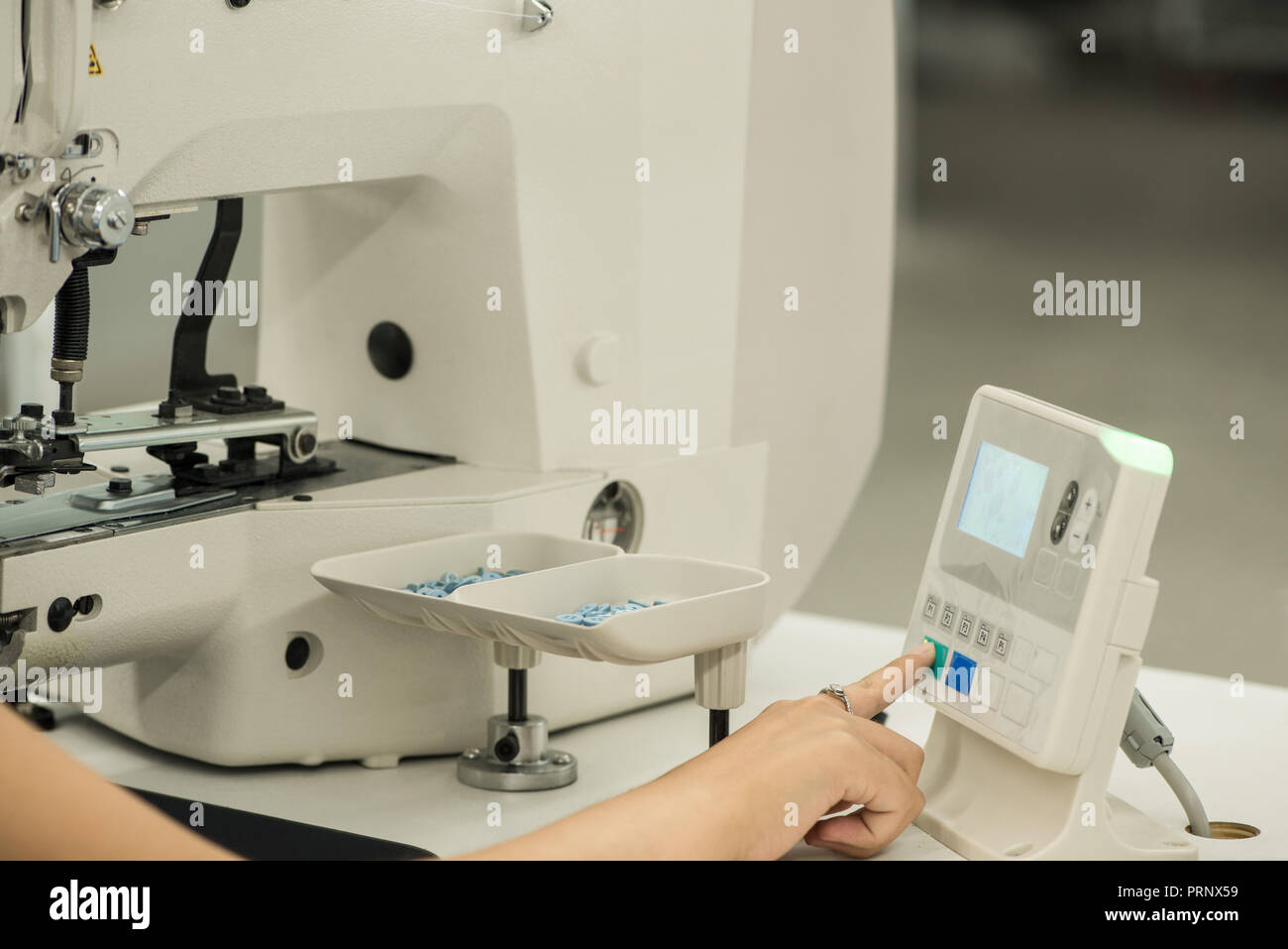 seamstress at work, controls the sewing machine through an electronic panel - Stock Image