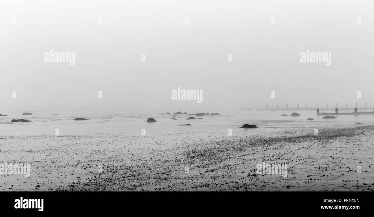 Monochrome Misty beach in the winter with rocks in the foreground and sea breaks behind - Stock Image