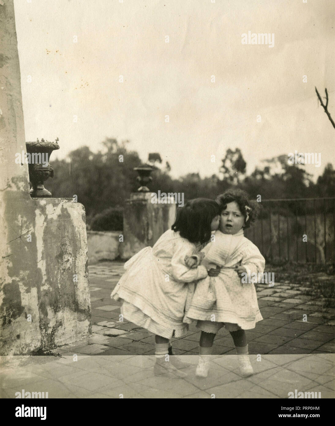 Two small girls playing outside, Italy 1908 - Stock Image