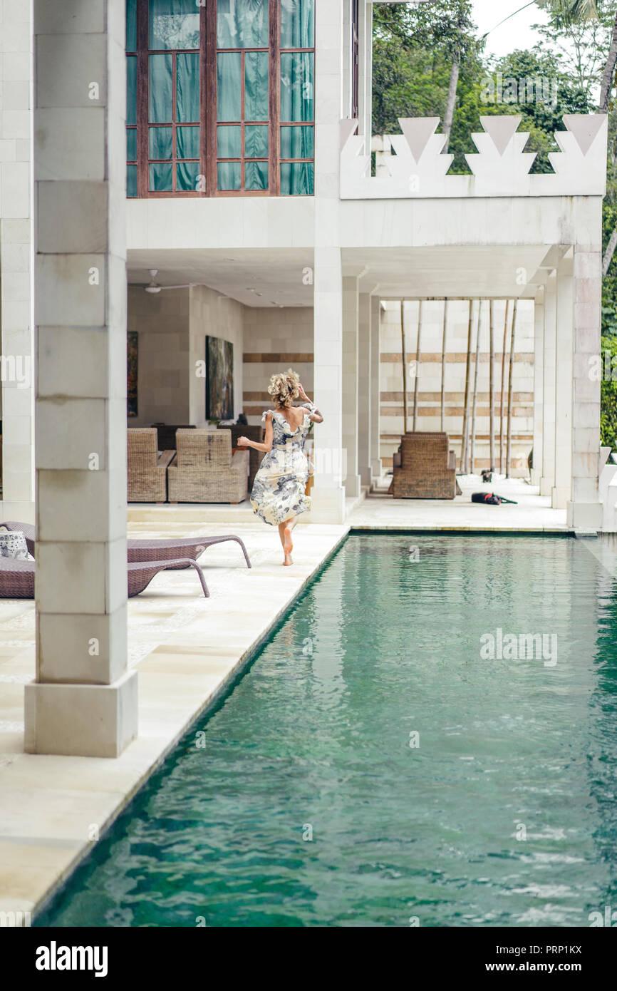 back view of woman in beautiful dress running near swimming pool at villa - Stock Image
