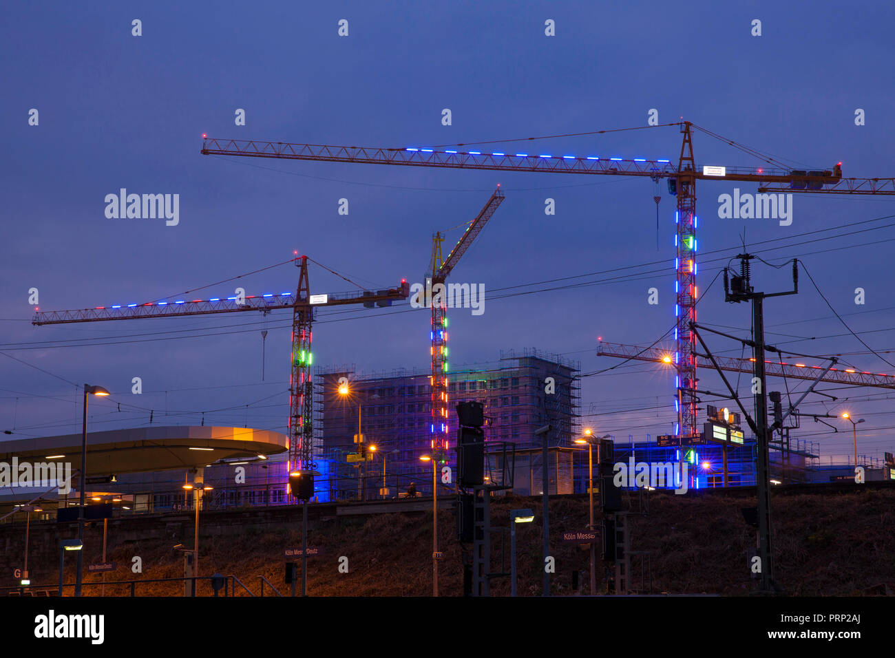 illuminated cranes on the the construction site of the building project MesseCity Koeln near the exhibition center in the district Deutz, in front of  - Stock Image