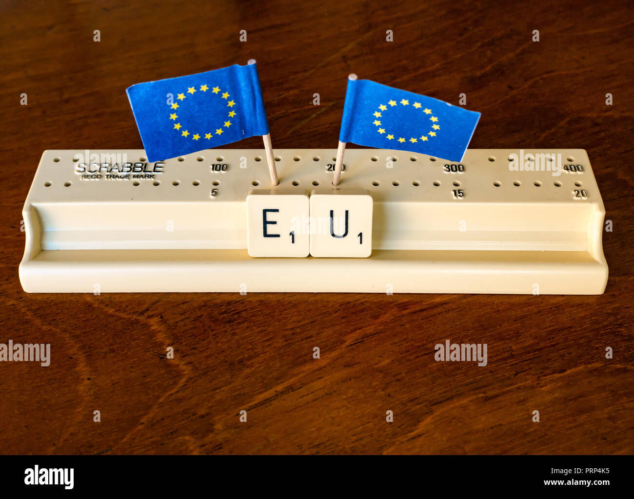 Scrabble letters spelling EU in Scrabble tray with European Union flags on dark mahogany background - Stock Image