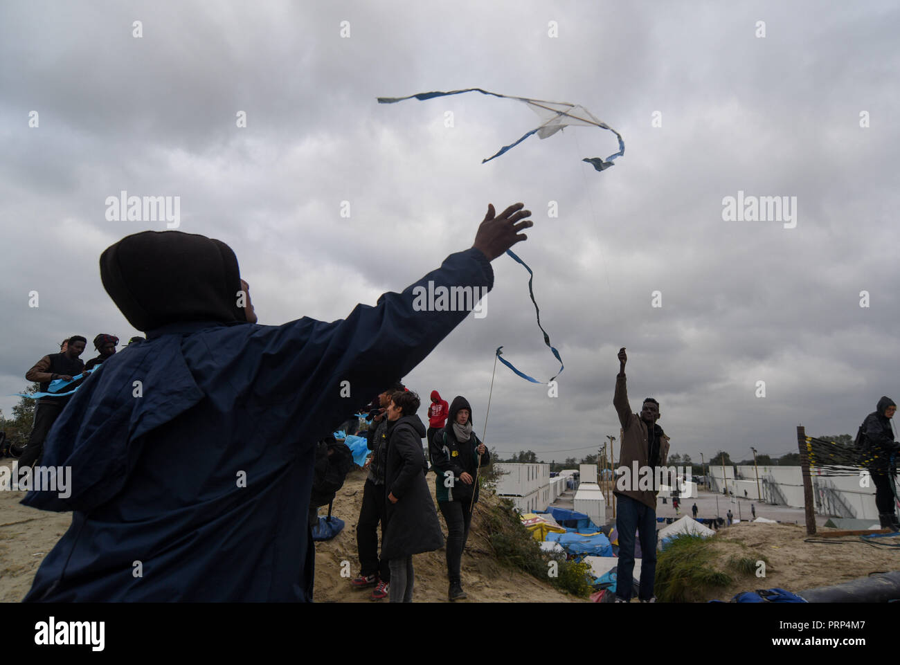 October 12, 2016 - Calais, France: Migrants play with kites in the Calais 'jungle' migrant camp. Scene de vie quotidienne dans la jungle de Calais, l'un des plus grands camps de migrants au monde. *** FRANCE OUT / NO SALES TO FRENCH MEDIA *** Stock Photo