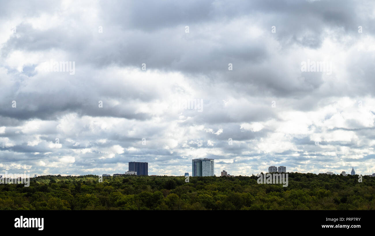 gray rainy clouds in sky over apartment houses and woods in autumn day - Stock Image