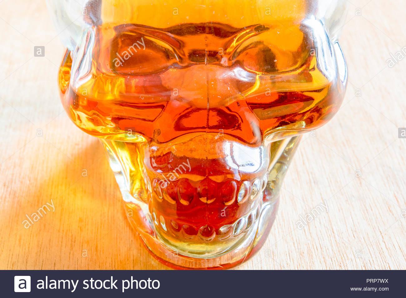 Dangers of drinking alcoholic beverages: Skull bottle full of rum - Stock Image