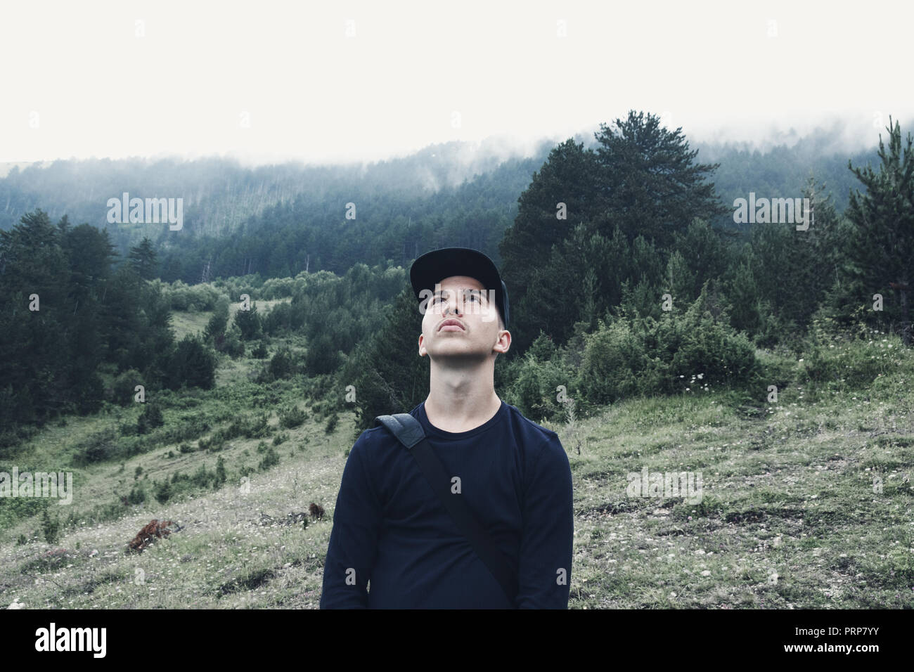 young hiker looking up to sky in front of forest and fog Stock Photo