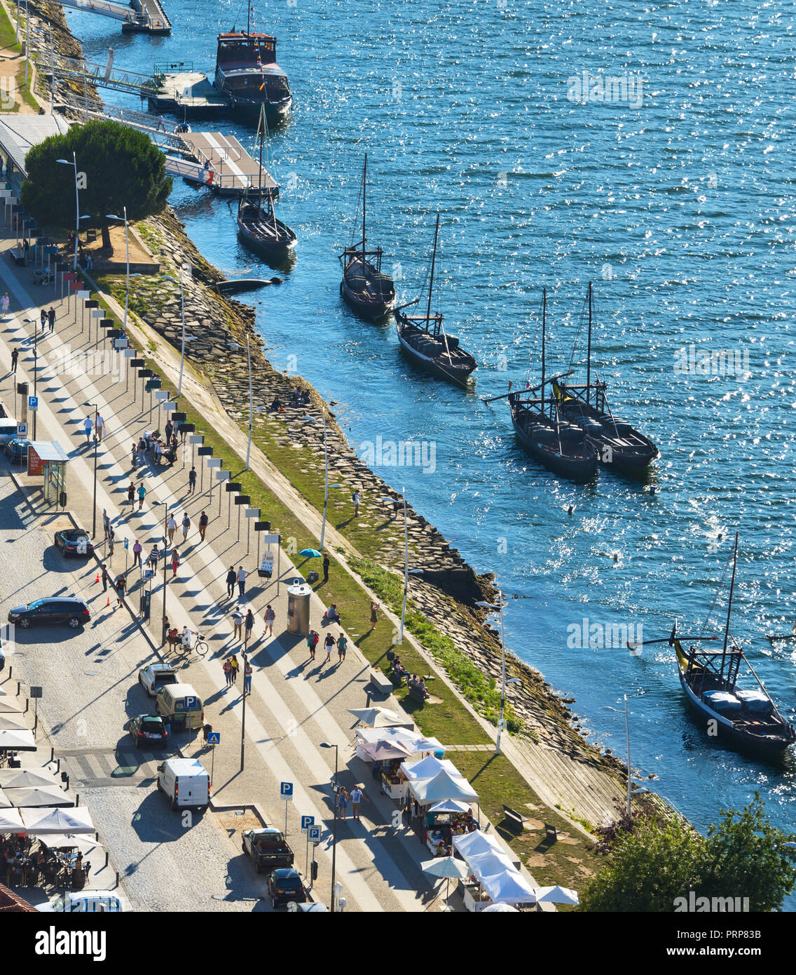 Aerial view of Vila Nova De Gaia with restaurants and traditional boats by embankment, Porto, Portugal - Stock Image