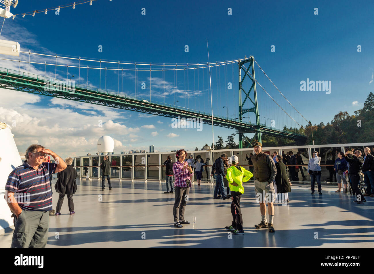 Cruise ship passengers on top deck of Holland America The Volendam, as it passes under The Lions Gate Bridge in Burrard Inlet, Vancouver, British Columbia, Canada enroute to Alaska, USA. - Stock Image