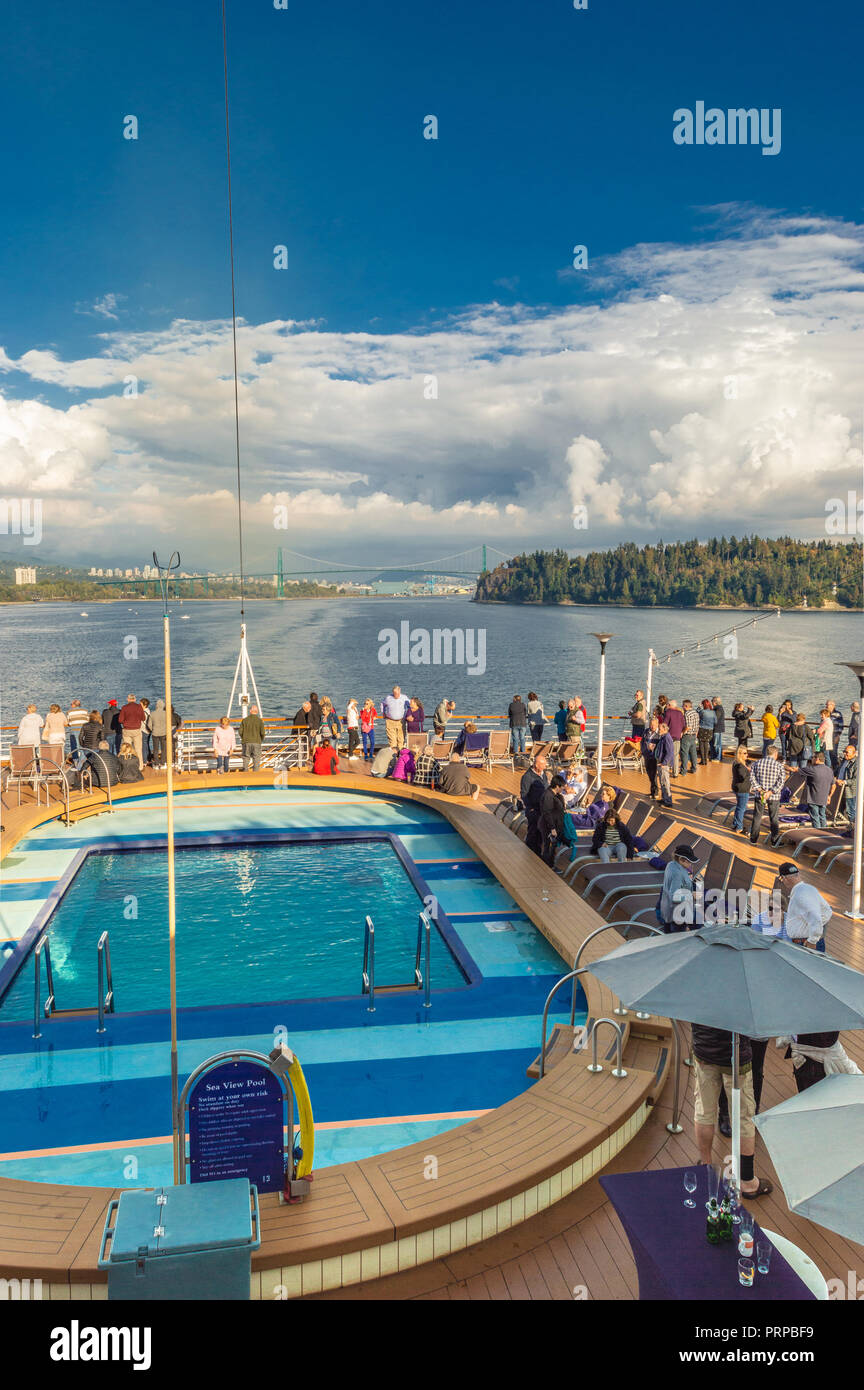 Cruise ship passengers on rear outdoor Lido deck beside The Seaview Pool of Holland America's The Volendam, as it sets sail from Vancouver, British Columbia, Canada enroute to Alaska, USA. - Stock Image