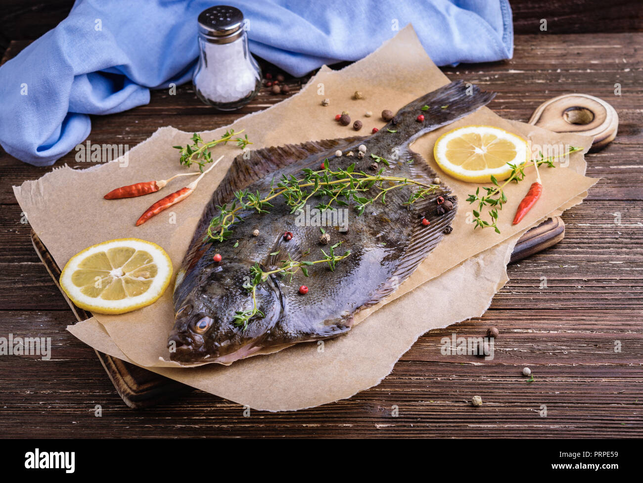 Raw flounder plaice fish (flatfish). Cooking process concept. Flounder fish with spices, lemon slices, thyme on parchment paper. Dark wooden table bac - Stock Image