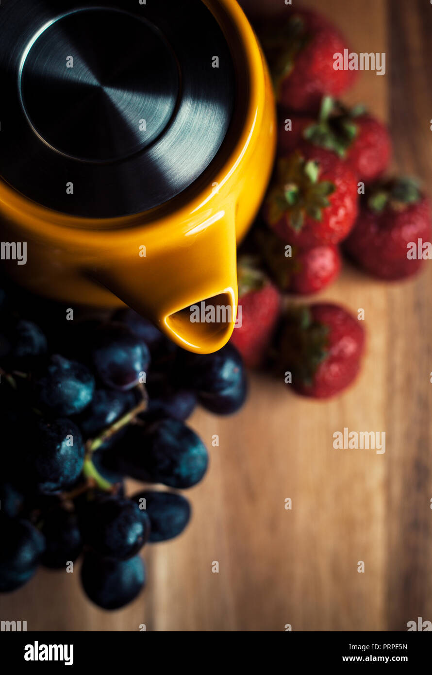 photo of a bright yellow teapot on a wooden table Stock Photo