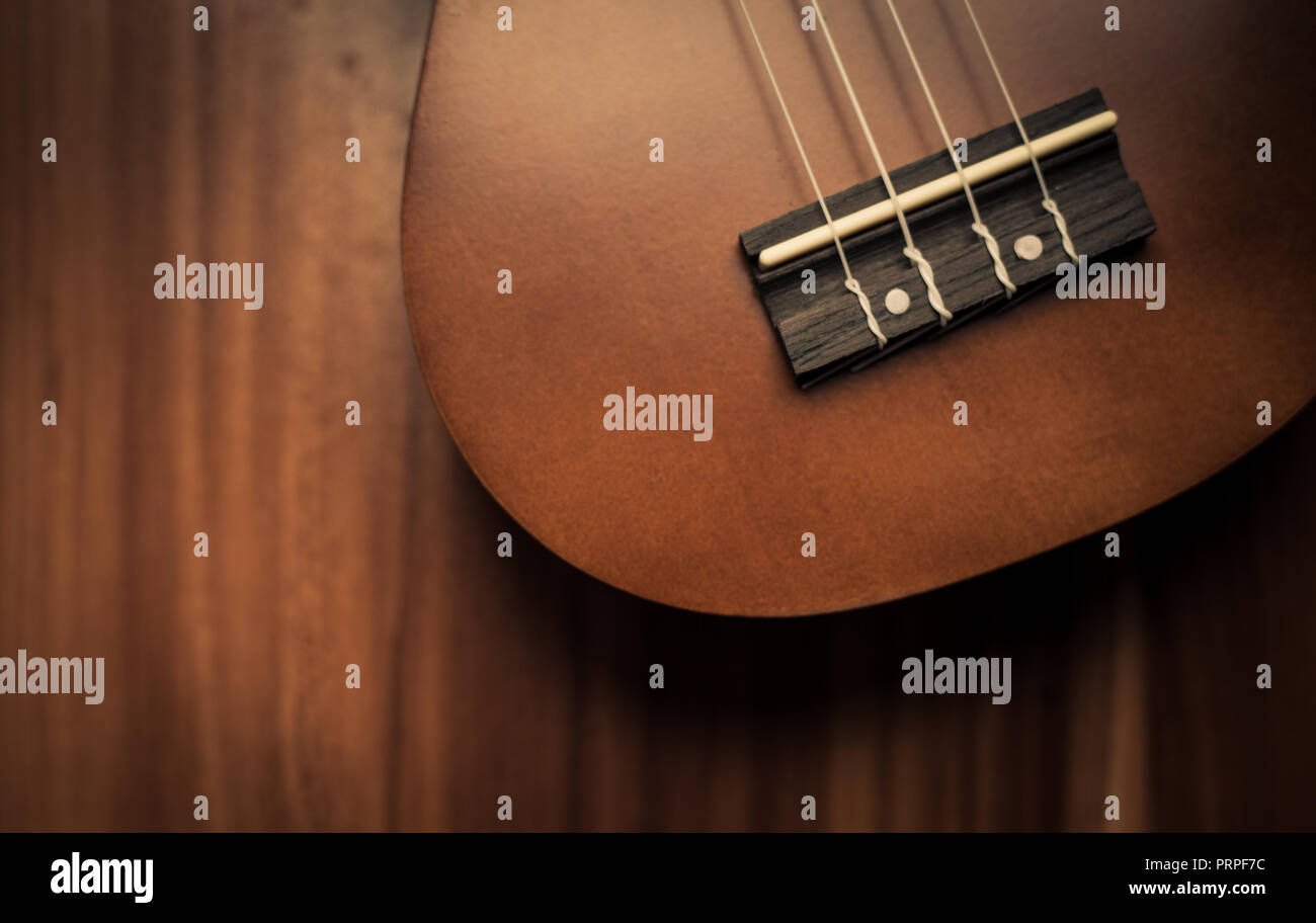 closeup photo of a ukulele against a brown background Stock Photo