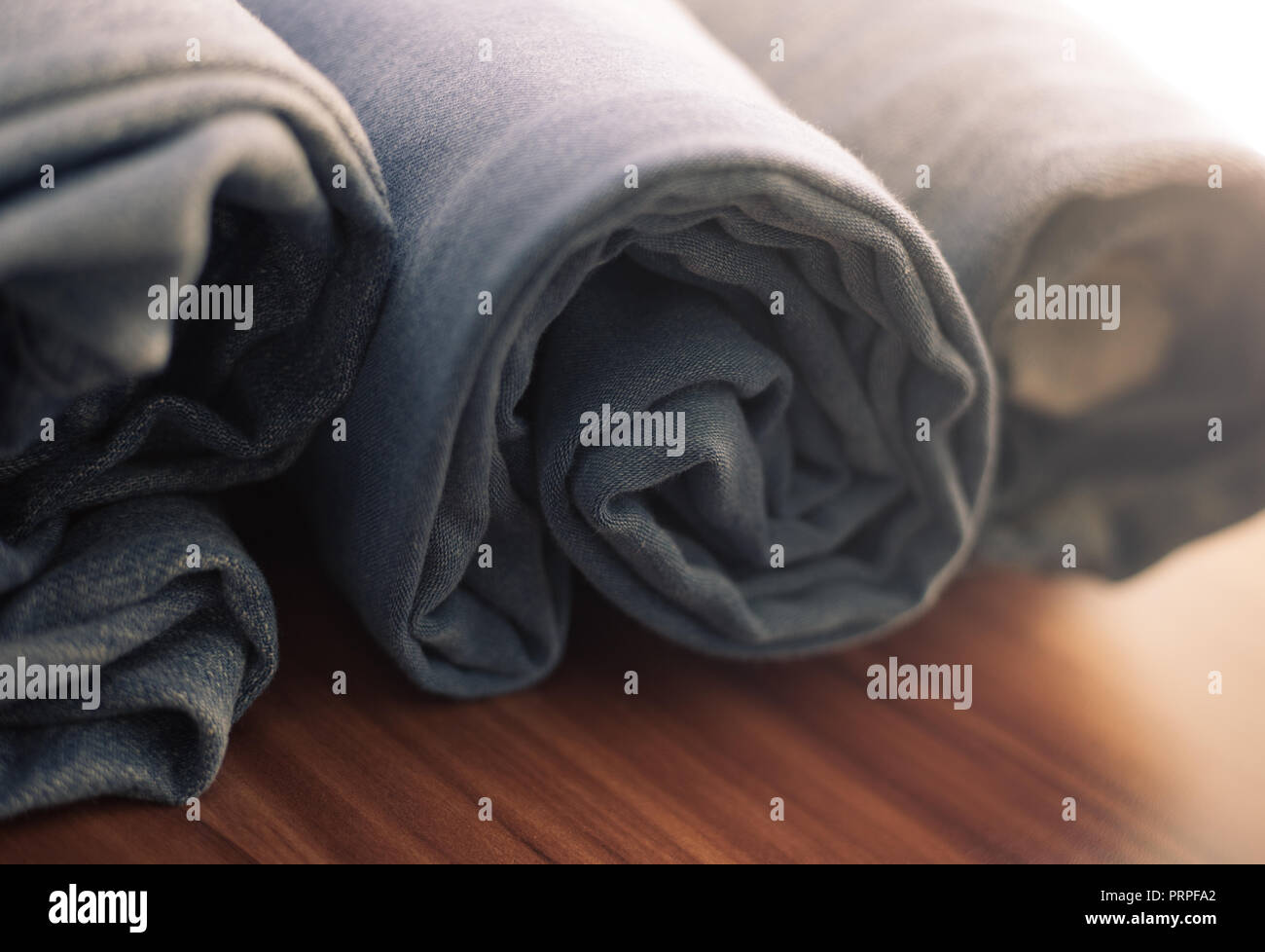 closeup photo of blue jeans rolled on a wooden table Stock Photo