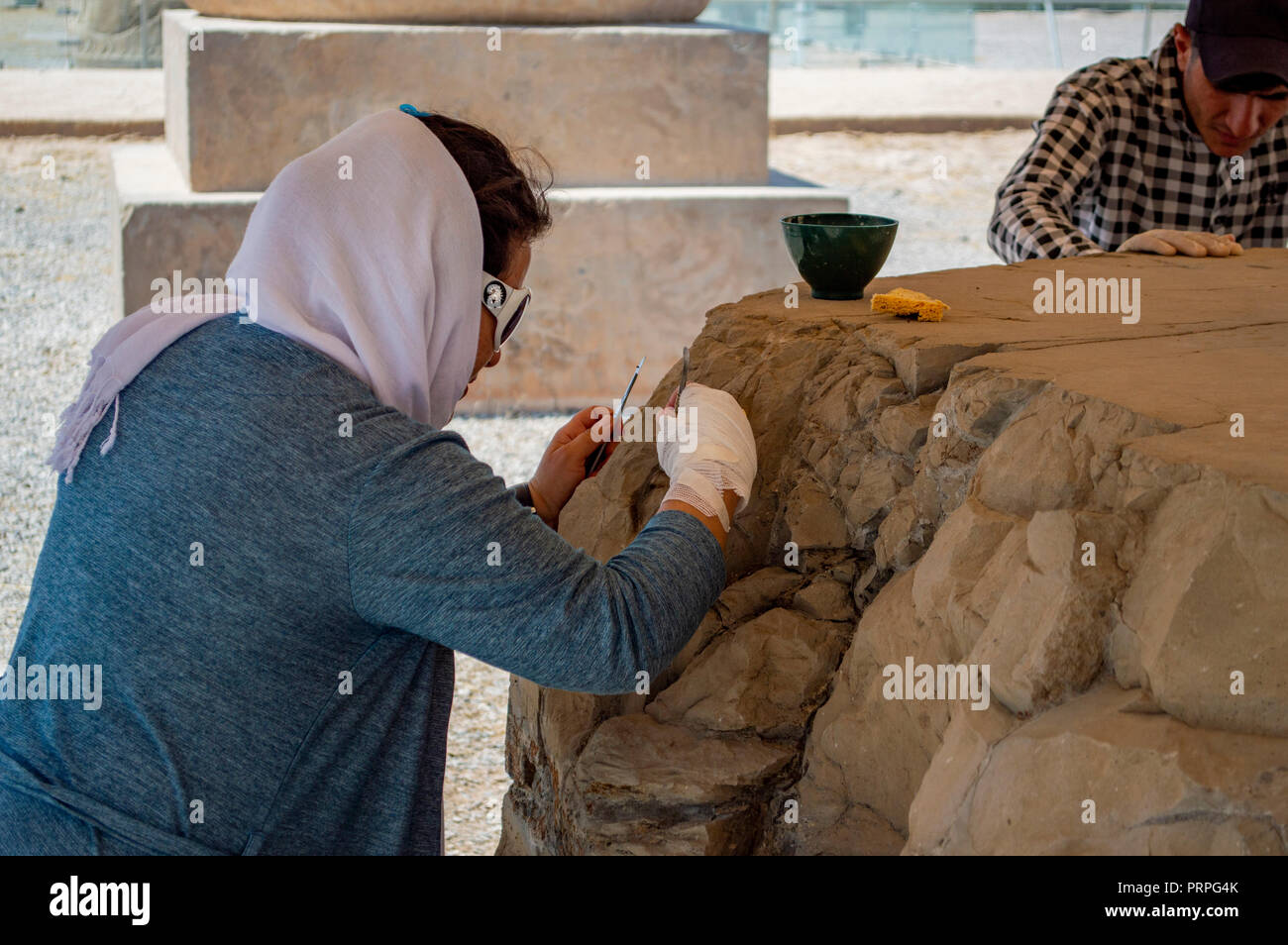 An archaeologist restoring a part of Persepolis, Iran - Stock Image