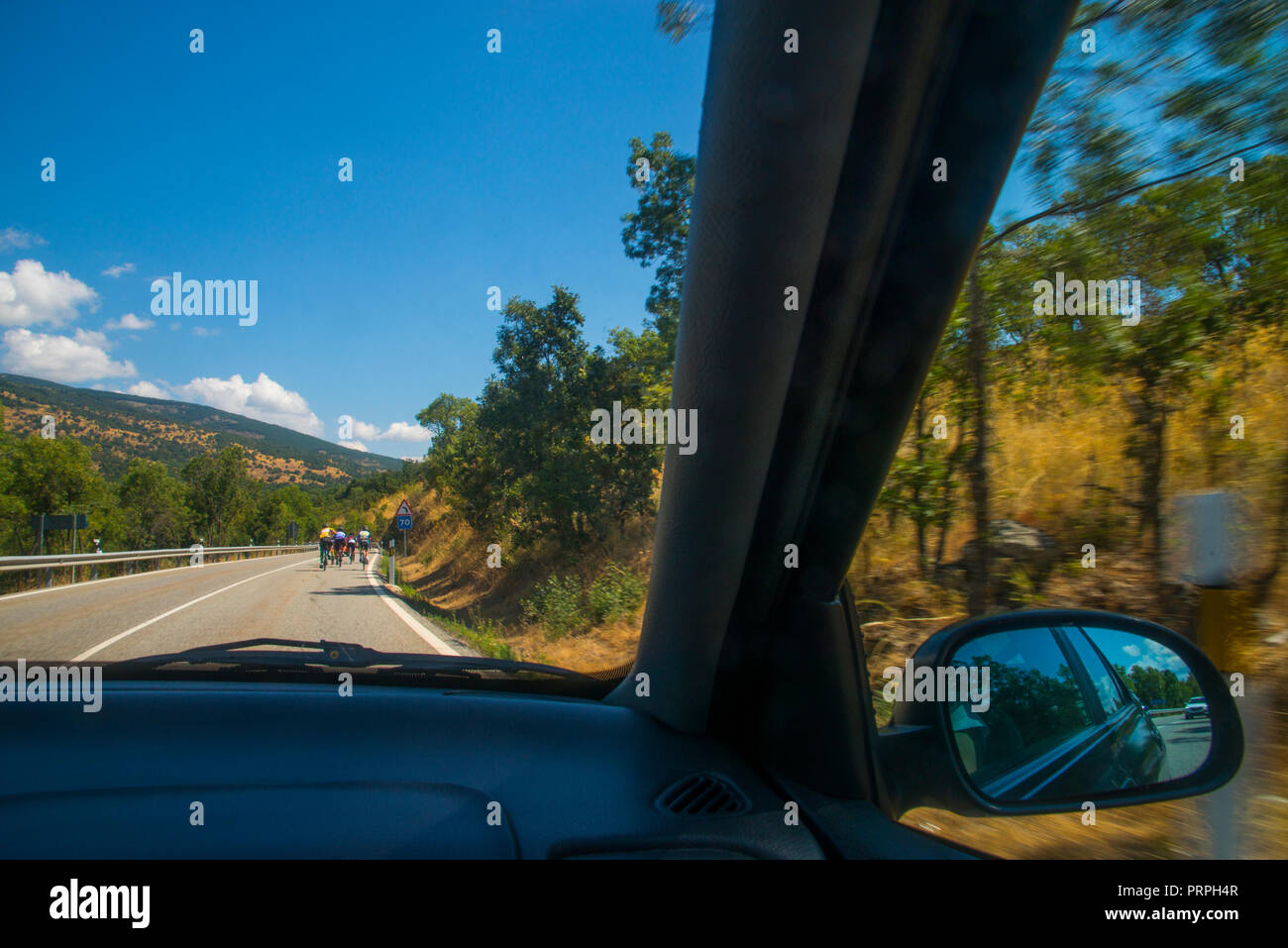 Group of ciclists traveling along a byway viewed from inside a car. - Stock Image