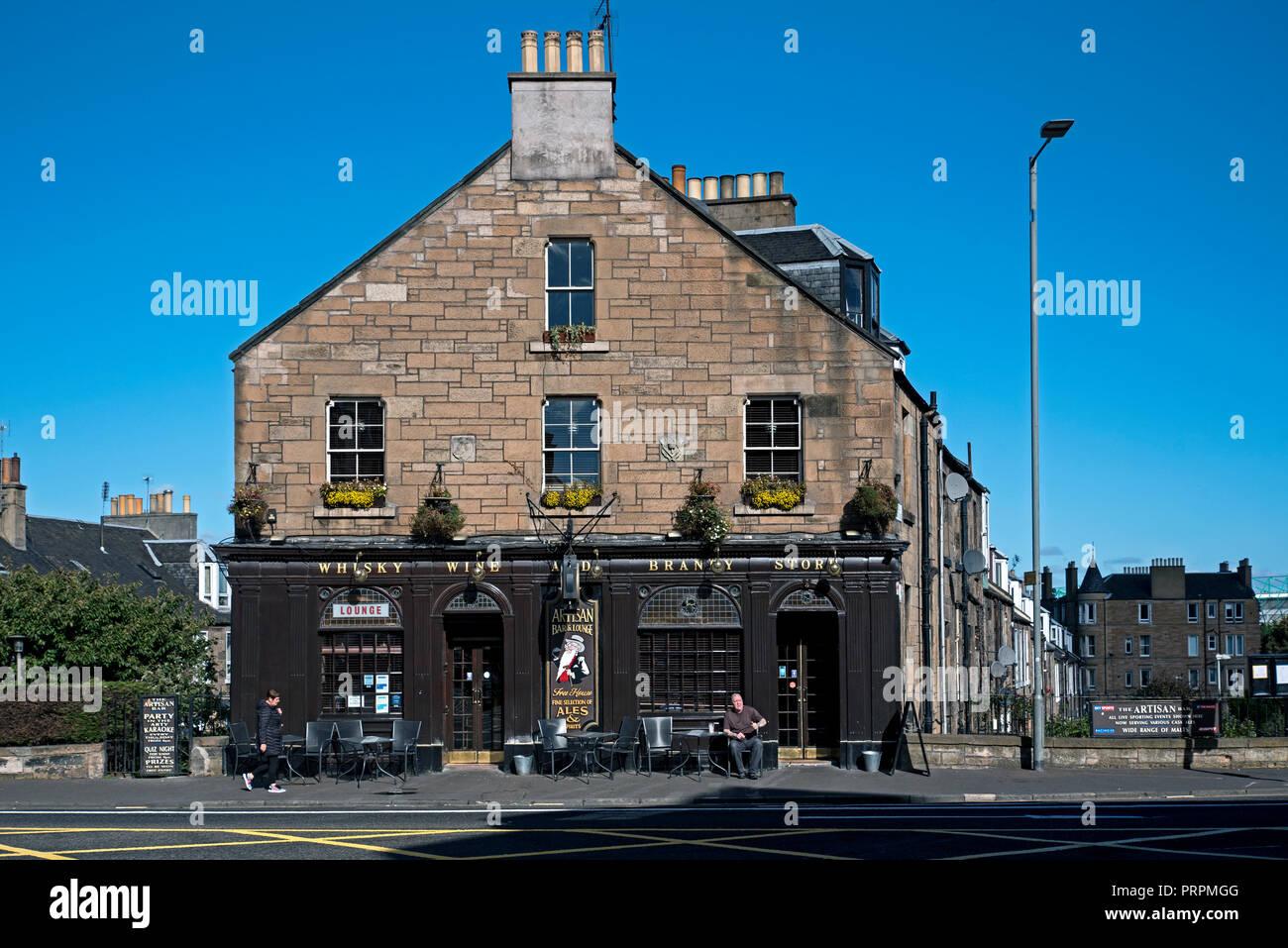 A single customer enjoys the sunshine outside the Artisan Bar on London Road, Edinburgh, Scotland, UK. - Stock Image