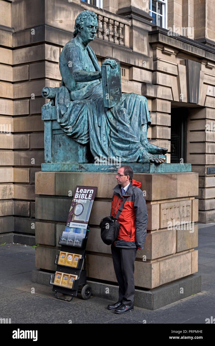 A member of Jehovah's Witnesses standing next to the statue of the Scottish Philosopher David Hume on the Royal Mile in Edinburgh, Scotland, Uk. - Stock Image