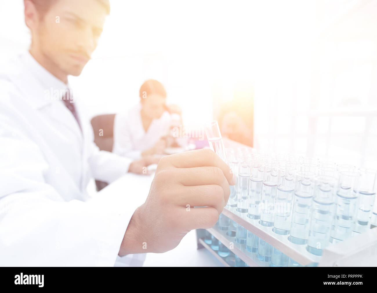 Beautiful medical doctors are working with test tubes and microscope at the lab Stock Photo