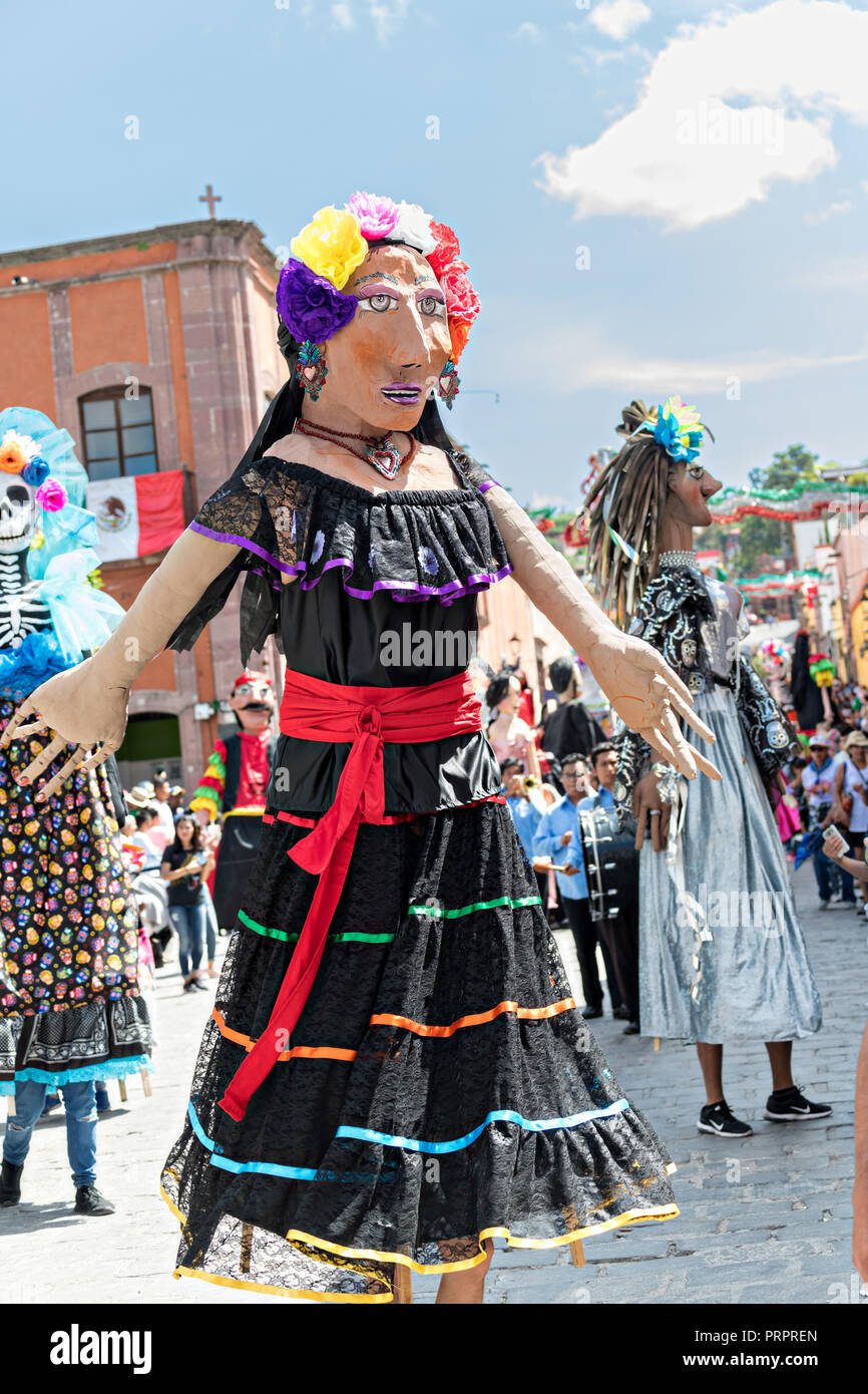 Giant paper-mache puppets called Mojigangas participate in the annual parade celebrating the cities patron saint during the Feast of Saint Michael September 30, 2018 in San Miguel de Allende, Mexico. The festival is a four-day long event with processions, parades and a late night fireworks battle. - Stock Image