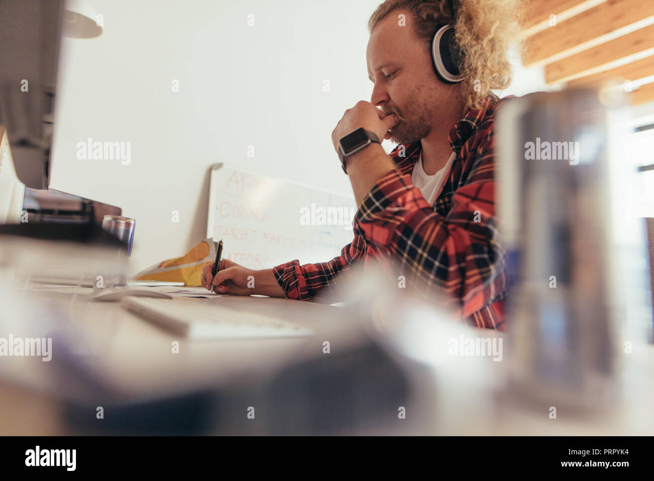 Man making some notes in copybook, sitting at small office table. Experience tech professional coding on a notepad in office. - Stock Image