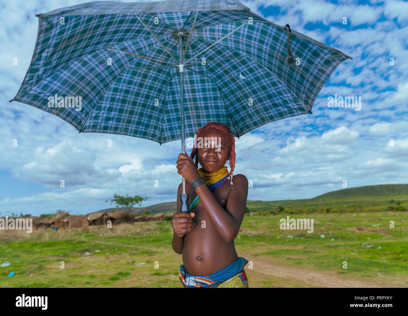 Mumuhuila tribe girl portrait holding an umbrella, Huila Province, Chibia, Angola Stock Photo