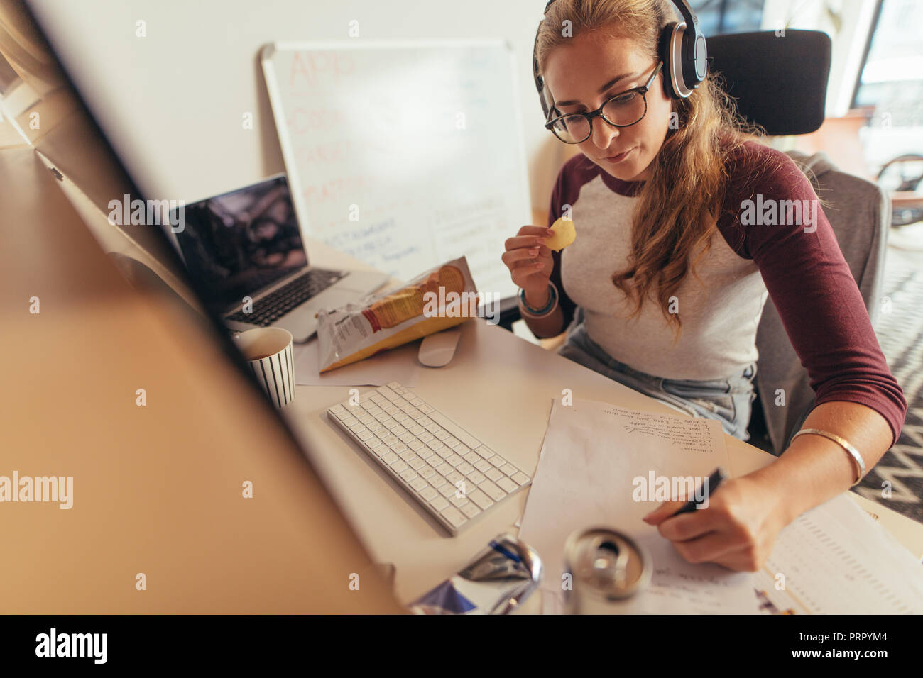 Woman writing programme codes on paper and eating. Female coder working on new software development at tech startup in office. - Stock Image