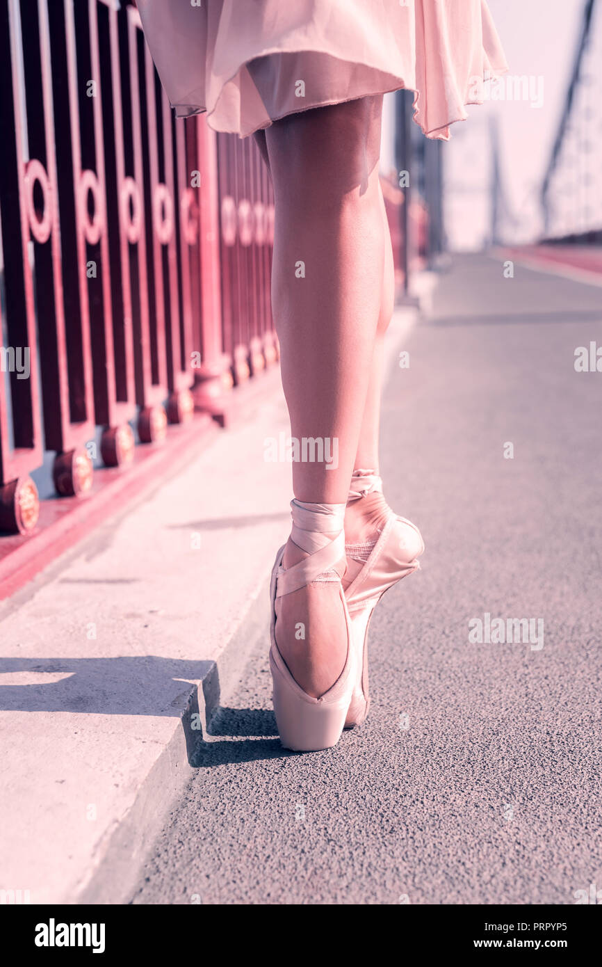 Beautiful nice ballerina wearing her pointe shoes Stock Photo