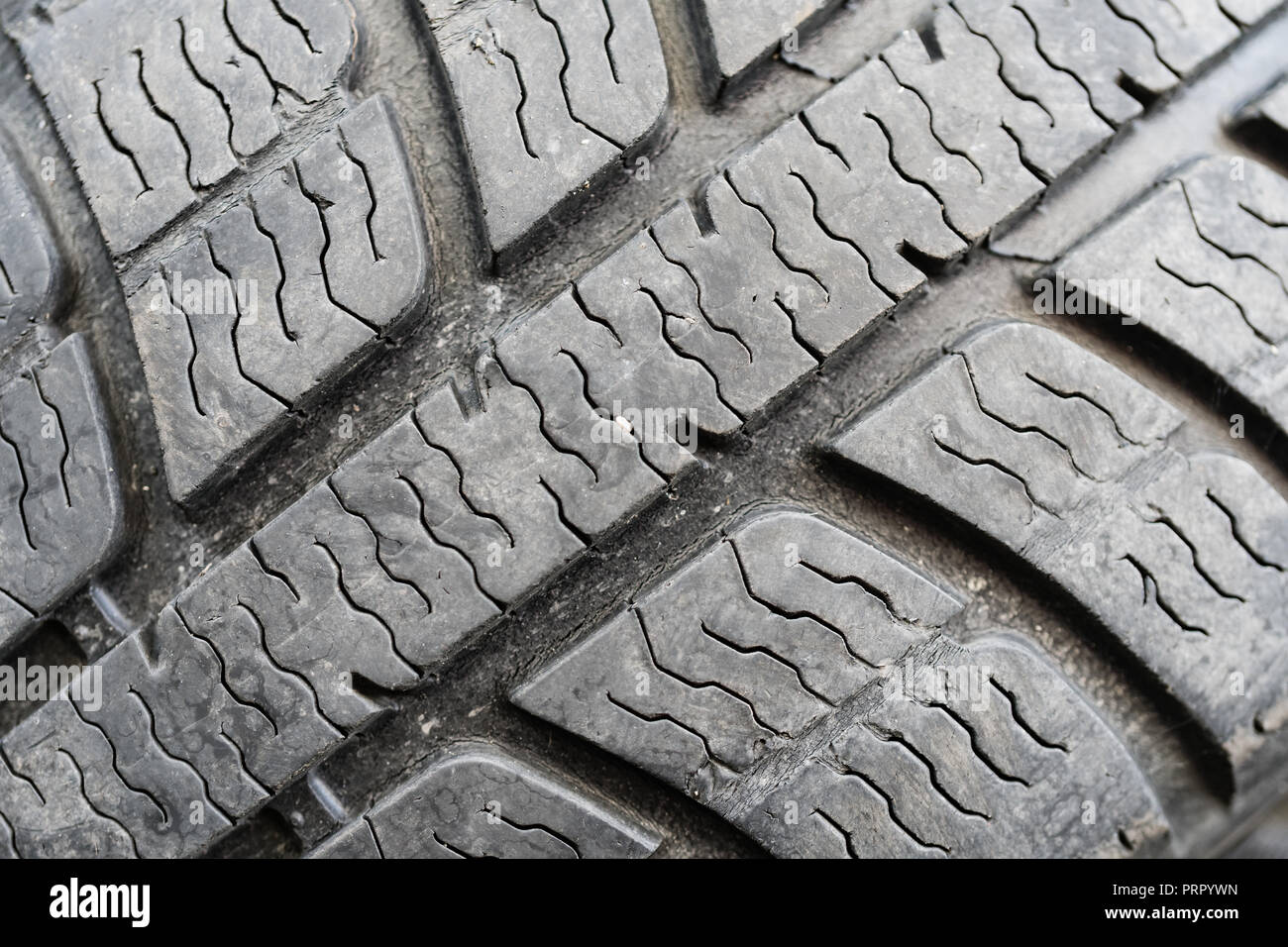 Closeup on worn out tire tread as a background. Evironmental friendly recycling concept. - Stock Image