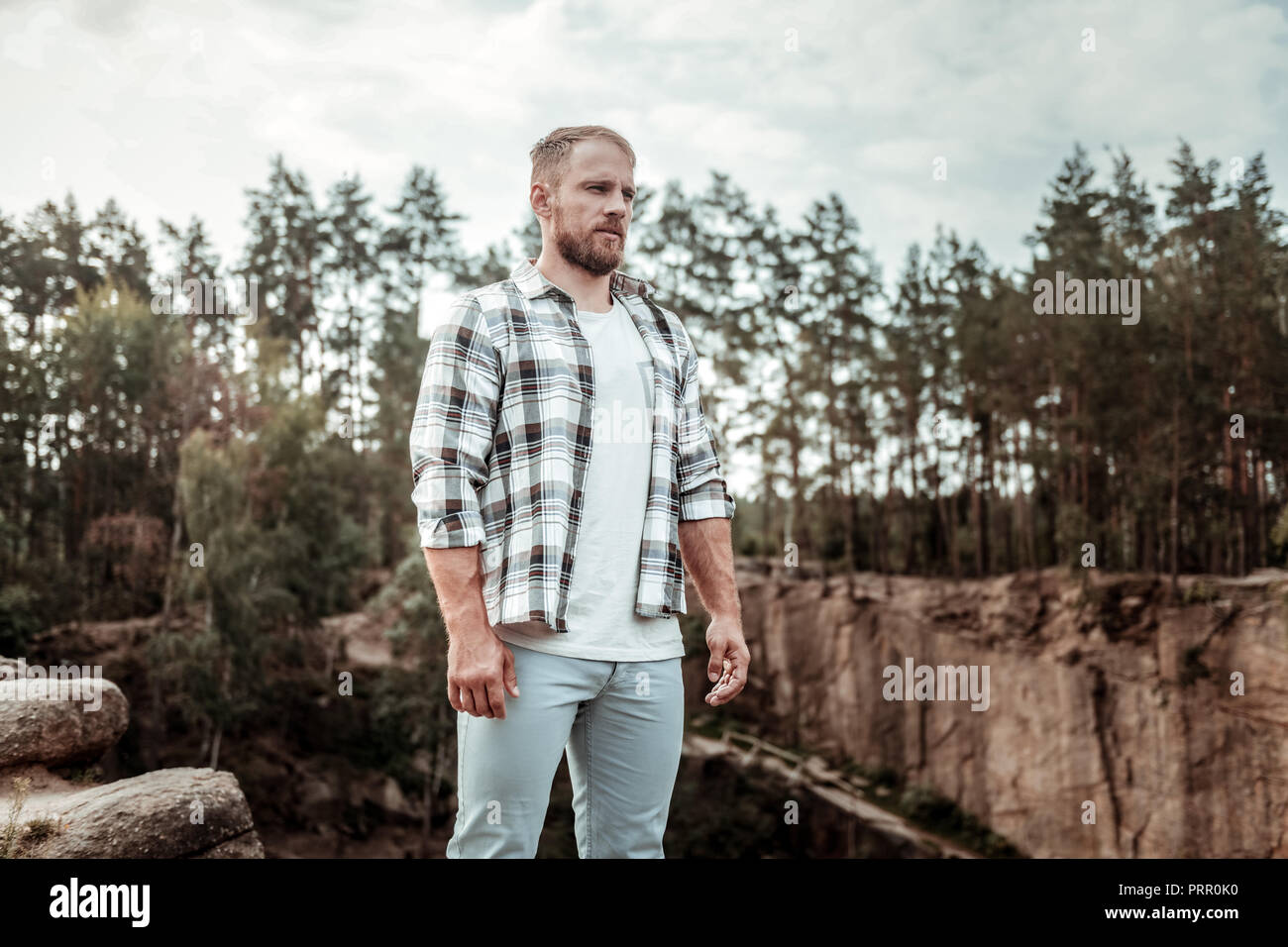 Bearded man wearing jeans and squared shirt standing in the rocky surroundings - Stock Image