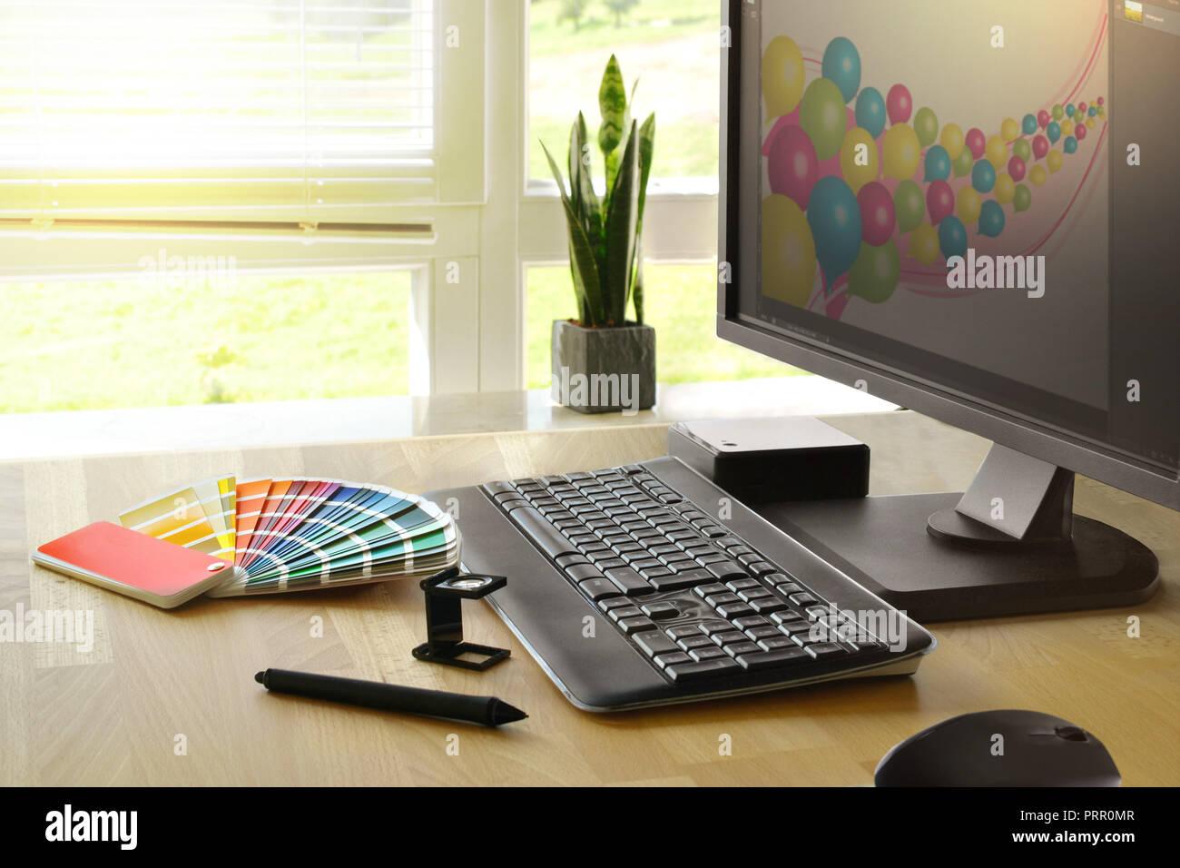 Schreibtisch eines Grafikers mit Monitor und Farbfaecher - Stock Image