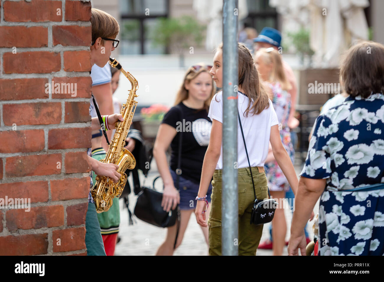 RIGA, LATVIA - AUGUST 18, 2018: A young guy on the street playing saxophone and earning money. - Stock Image