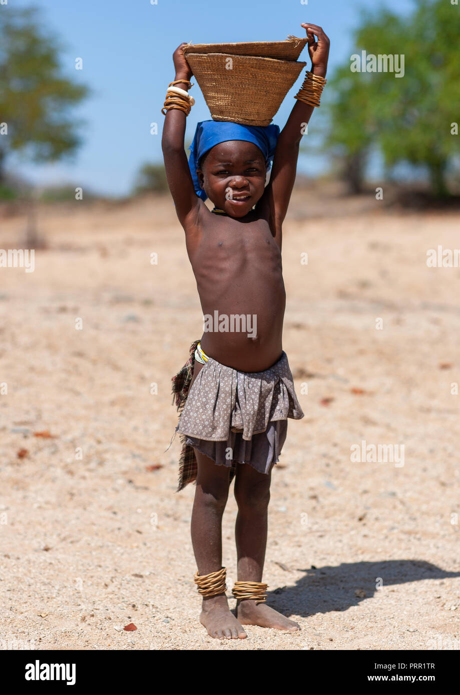 Mucubal tribe girl carrying a basket on head, Namibe Province, Virei, Angola Stock Photo