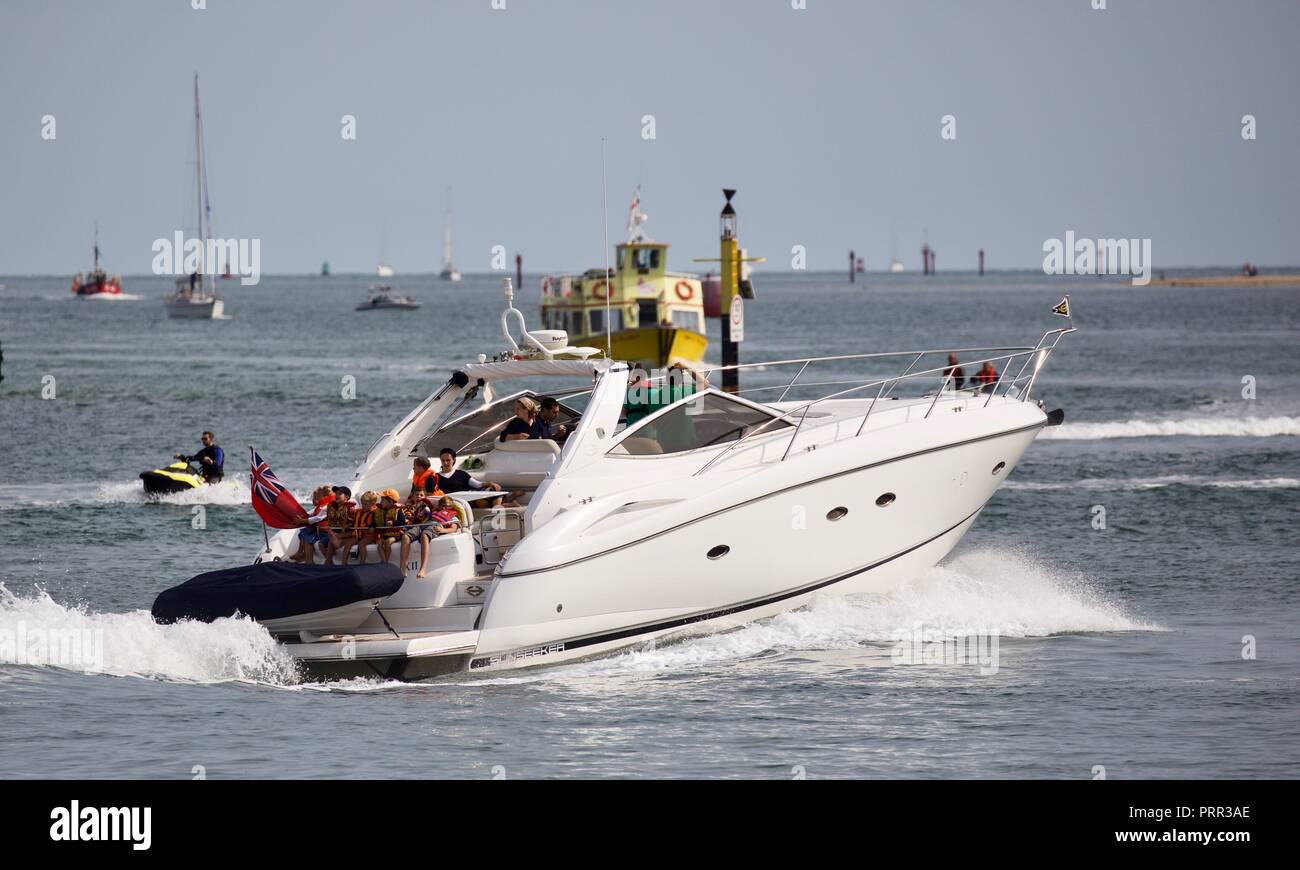 People enjoying a trip on a stunning Sunseeker luxury Yacht in Poole Harbour - Stock Image