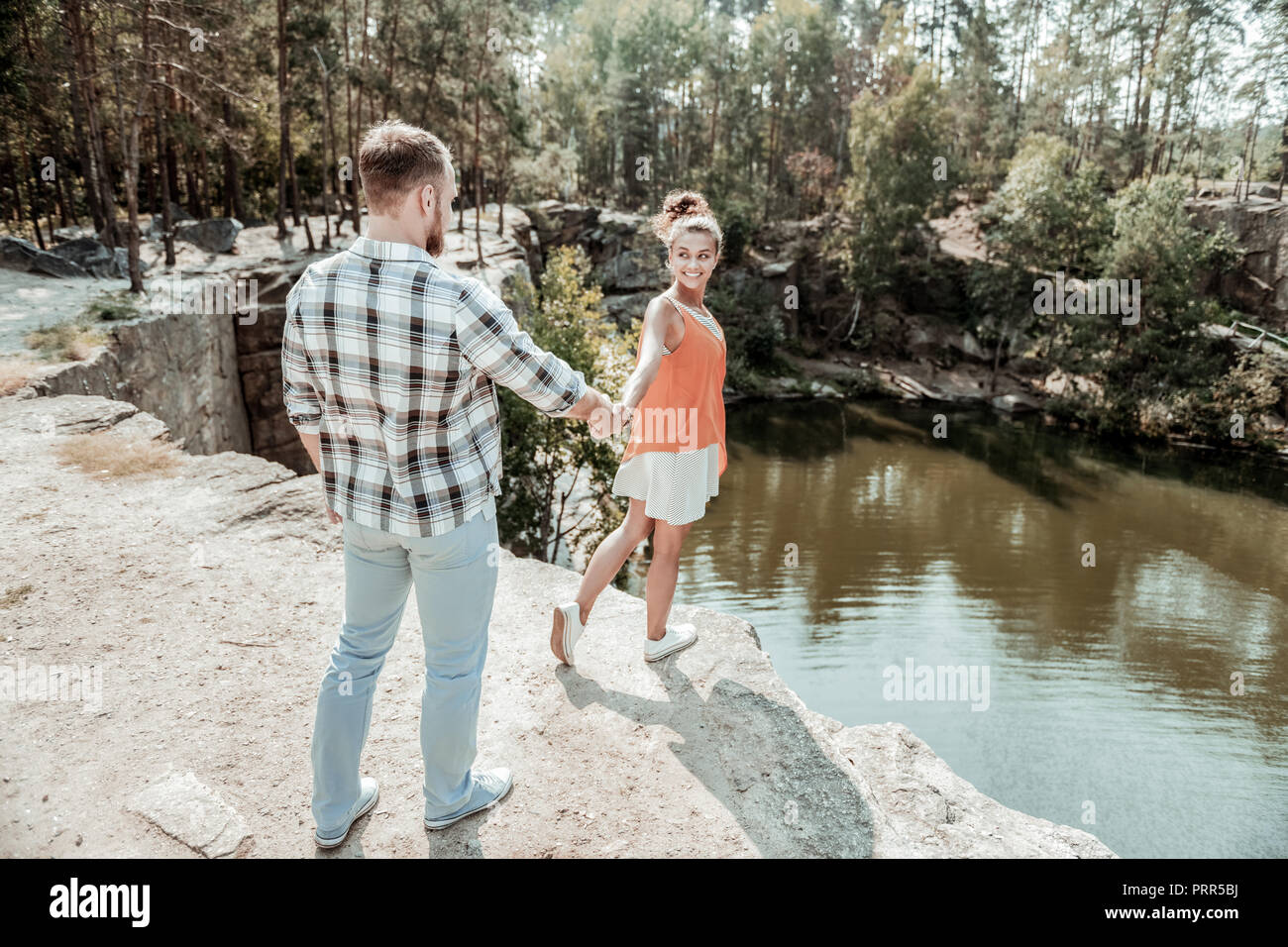 Strong supportive man holding hand of his beaming girlfriend coming closer to lake - Stock Image