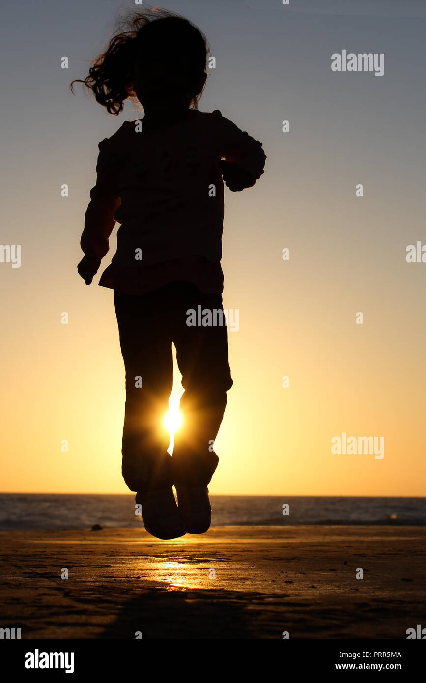 Sun captured in girl's jumping silhouette - Stock Image