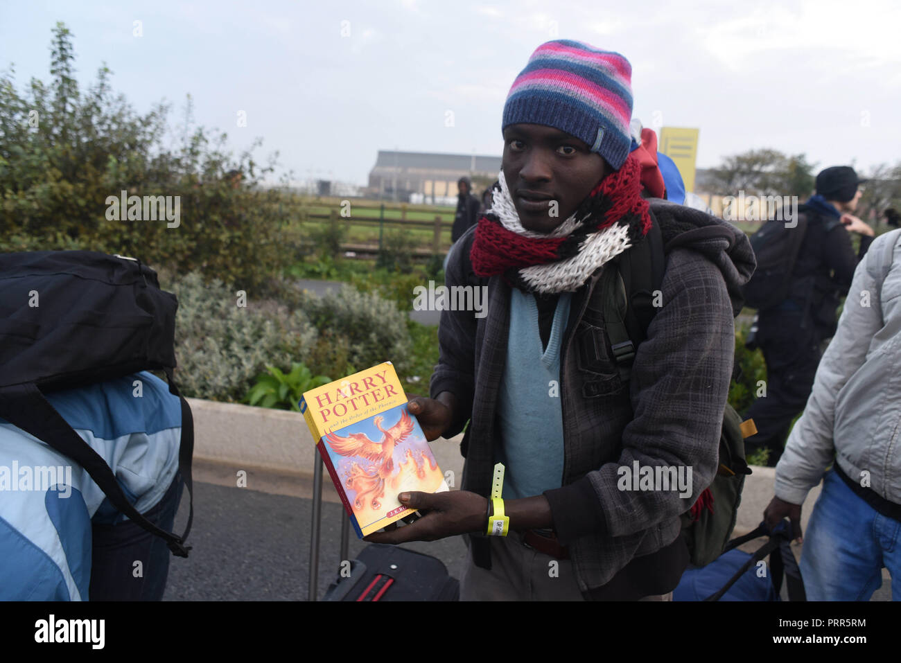 October 24, 2016 - Calais, France: Portrait of Saddam, a 25-year-old Sudanese migrant who is waiting in line to evacuate the Calais 'jungle' migrant camp. On this picture, Saddam shows a Harry Potter book in English language that he's carrying with him. Demantelement de la jungle de Calais, l'un des plus grands camps de migrants au monde. *** FRANCE OUT / NO SALES TO FRENCH MEDIA *** - Stock Image