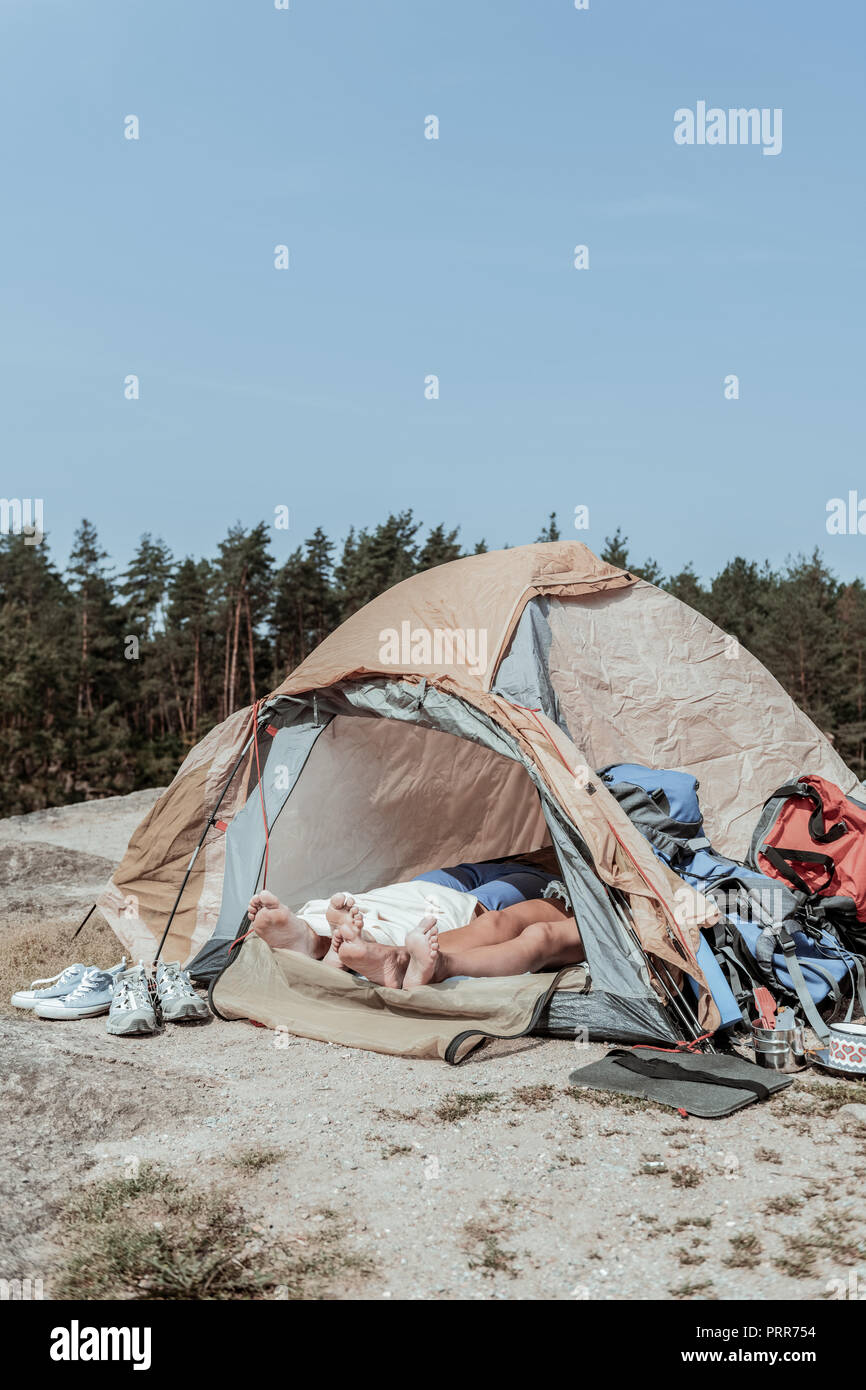 Couple of barefooted backpackers having some rest while lying in big tent - Stock Image