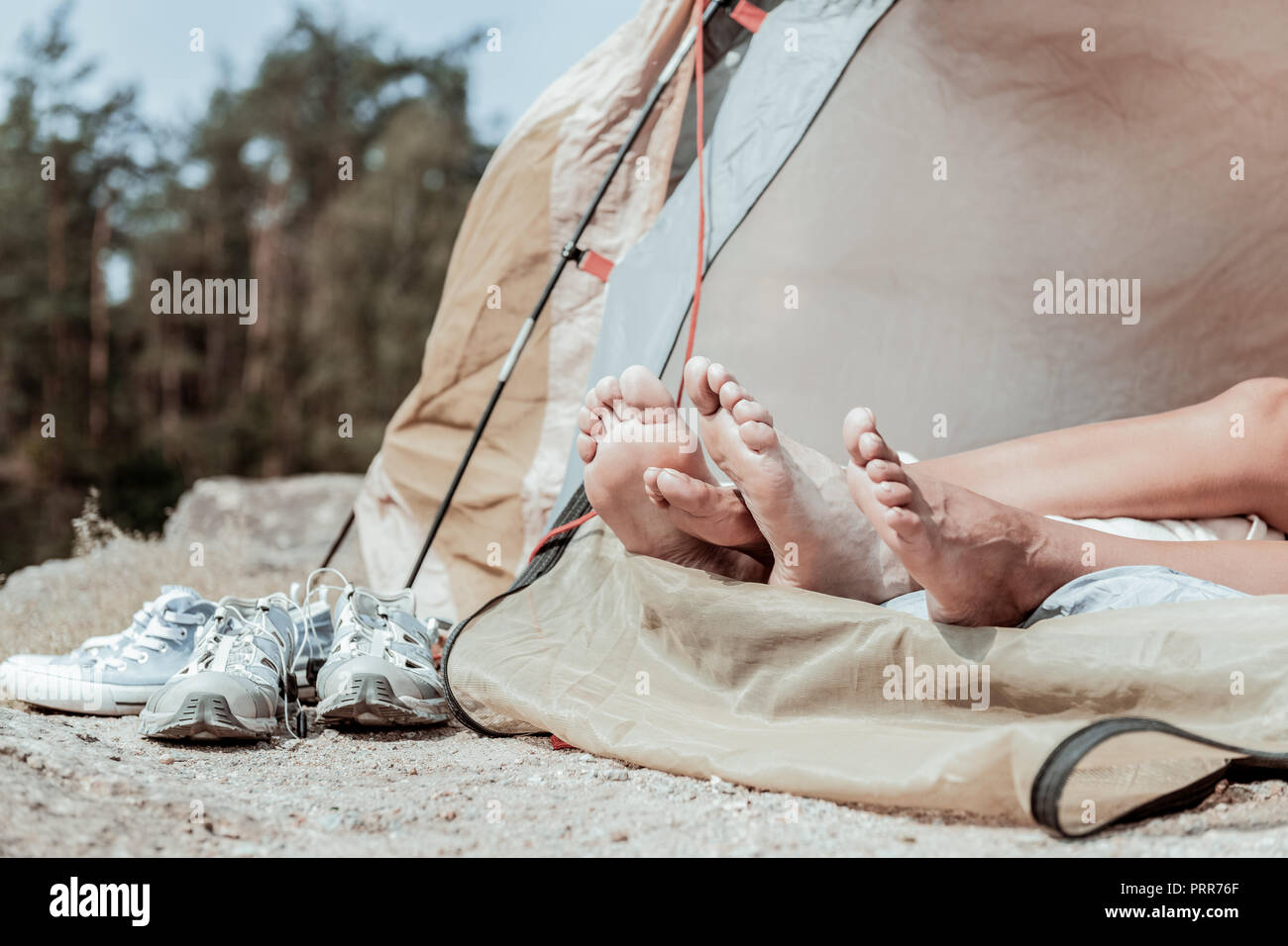 Close up of barefooted backpackers lying in tent standing near their sneakers - Stock Image