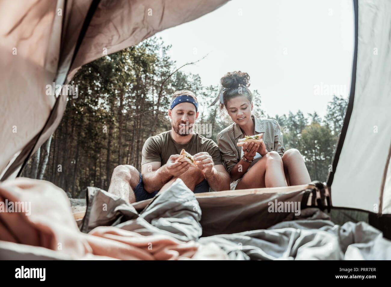 Caring loving girlfriend making some sandwiches with lettuce after waking in tent - Stock Image