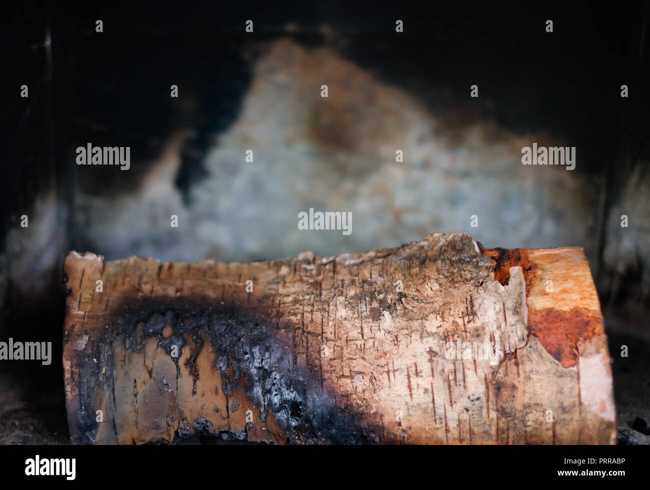 A bit burnt firewood lies in the fireplace or stove against the background of a wall covered with soot. - Stock Image