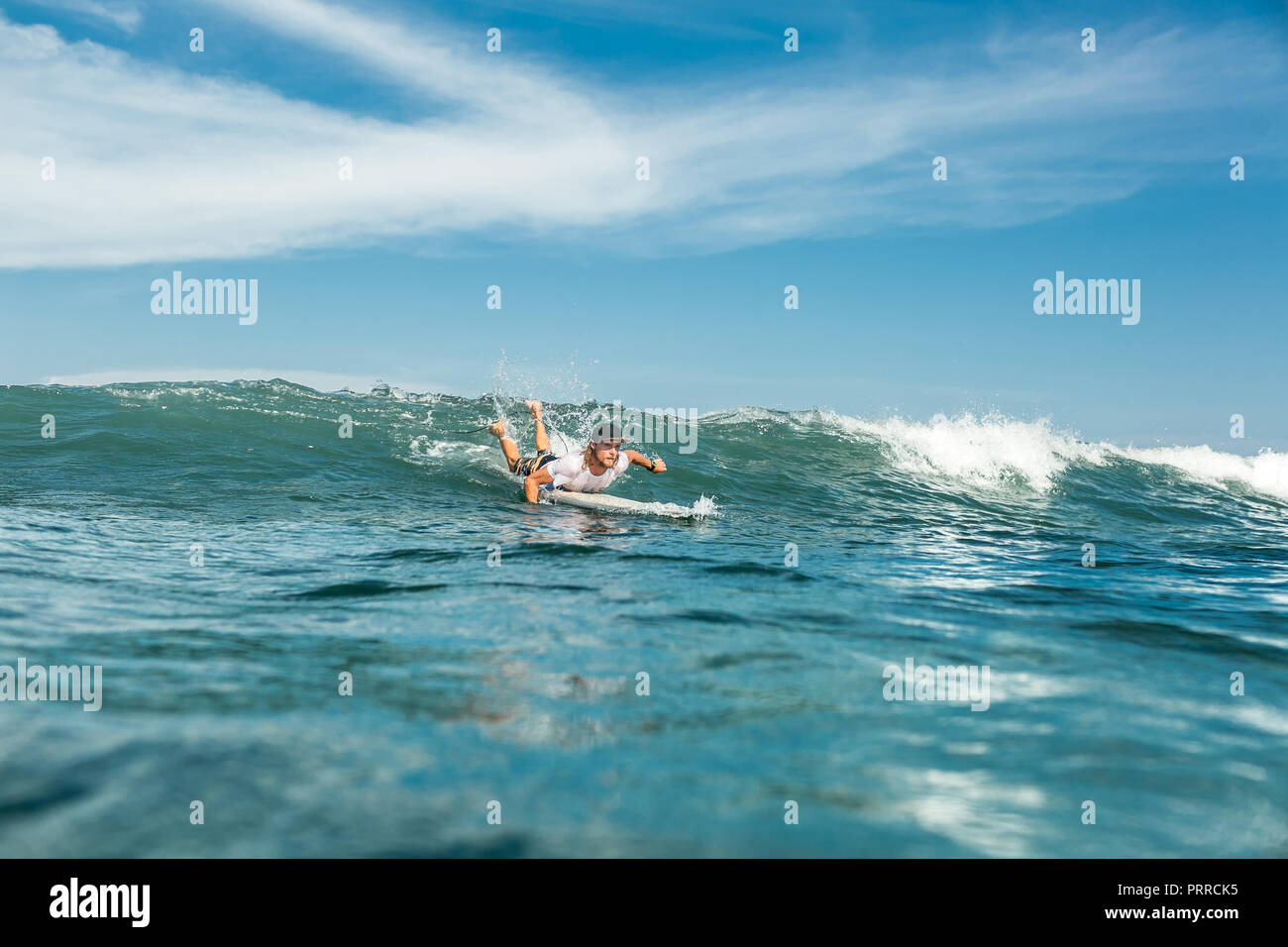 distant view of male sportsman swimming on surfing board in ocean at Nusa Dua Beach, Bali, Indonesia - Stock Image