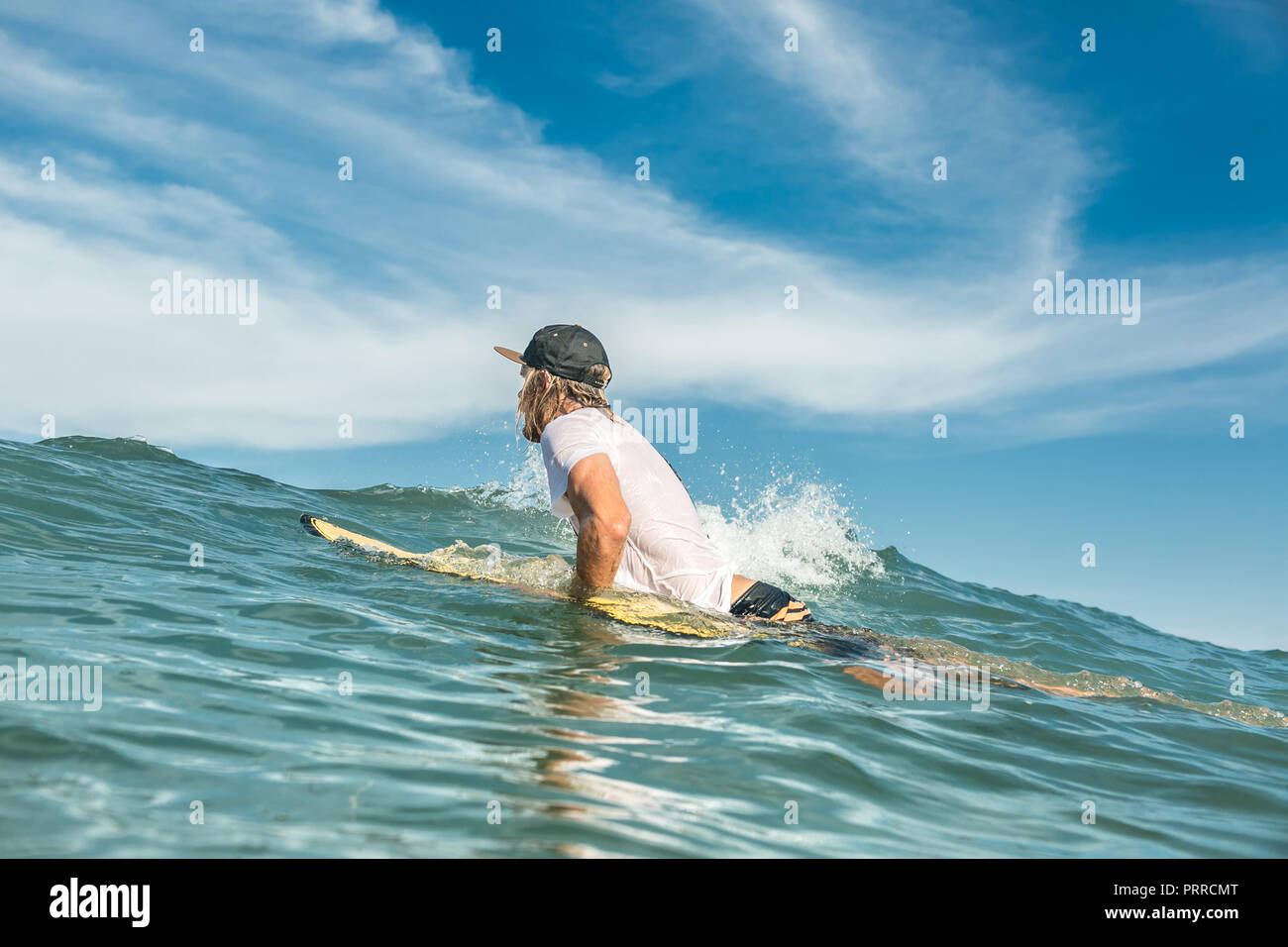 side view of male surfer swimming on surfing board in ocean at Nusa Dua Beach, Bali, Indonesia - Stock Image