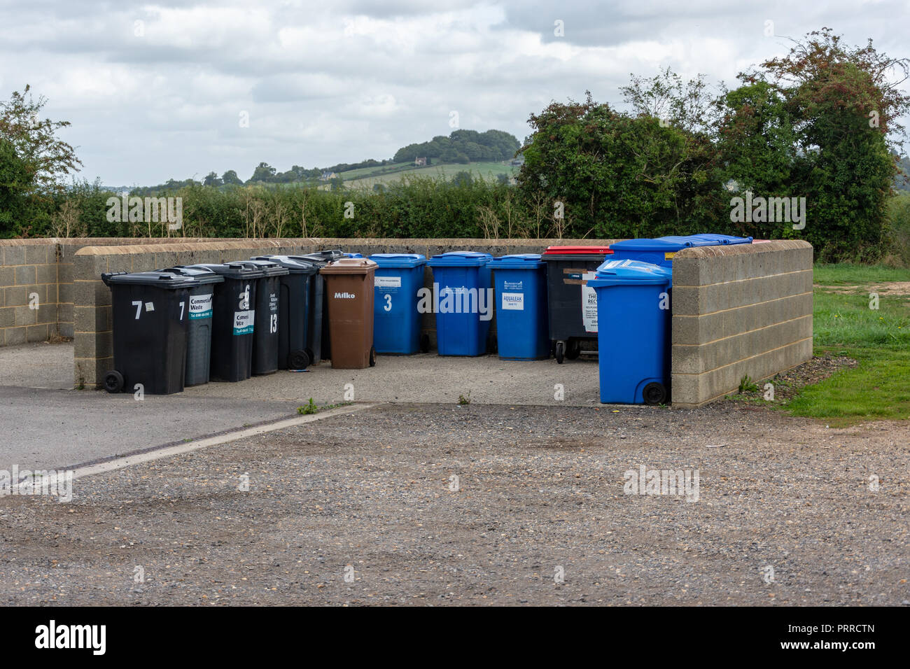 Small enclosure compound for rubbish bins and recycling bins separate from the units in a business park - Stock Image